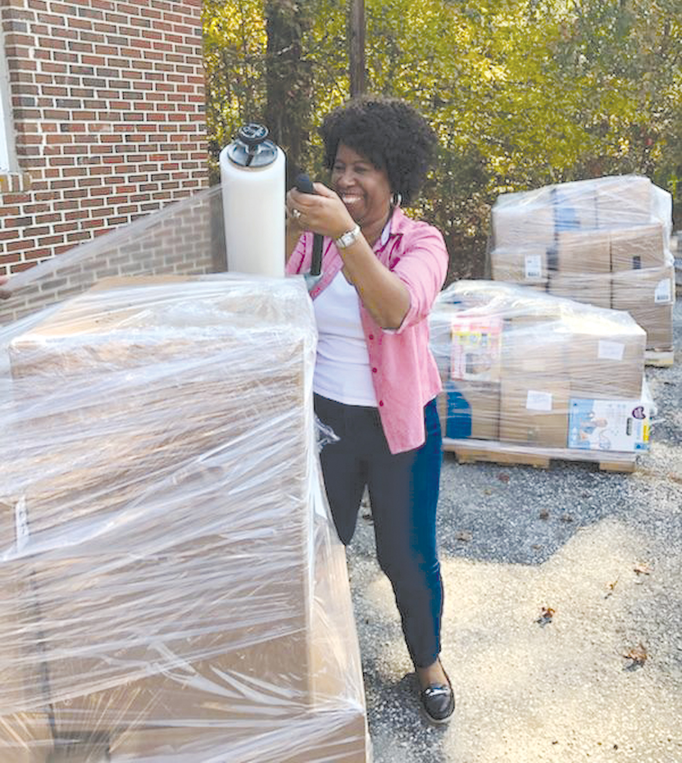 Grant Hill Missionary Baptist Church member Gladys Grant plastic wraps relief supplies together at the church recently.