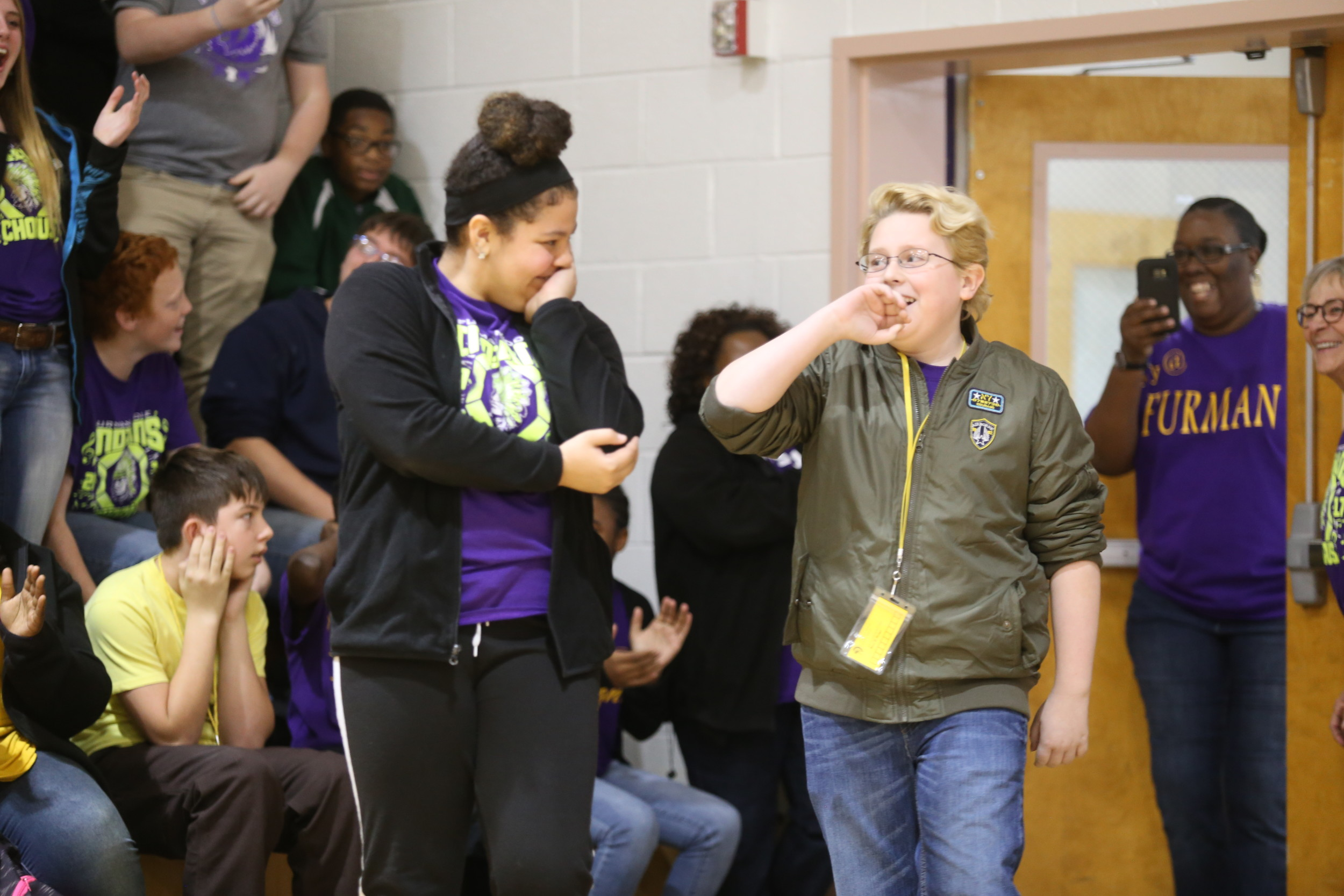 "BRUCE MILLS / THE SUMTER ITEM  Furman Middle School seventh-graders Taylor Gooden, left, and Quinn Welsh look stunned Friday as they enter the school's gym for a surprise sendoff celebration.  The two are auditioning today in Savannah, Georgia, for ""America's Got Talent."""