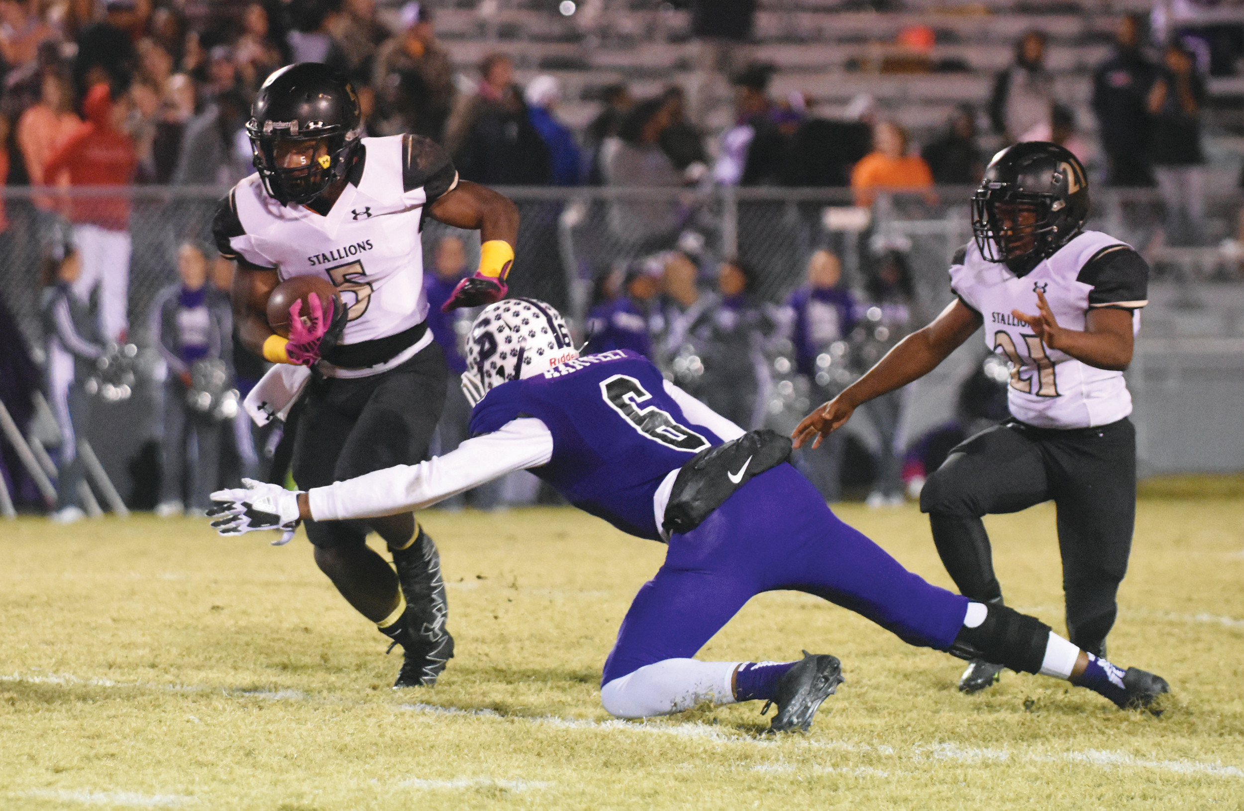 Lee Central running back Demetrius Dubose (5) avoids the tackle of Saluda's Raquon Hartley during the Stallions' 30-26 loss to Saluda in the quarterfinals of the 2A state playoffs on Friday at Bettis Herlong Stadium in Saluda.