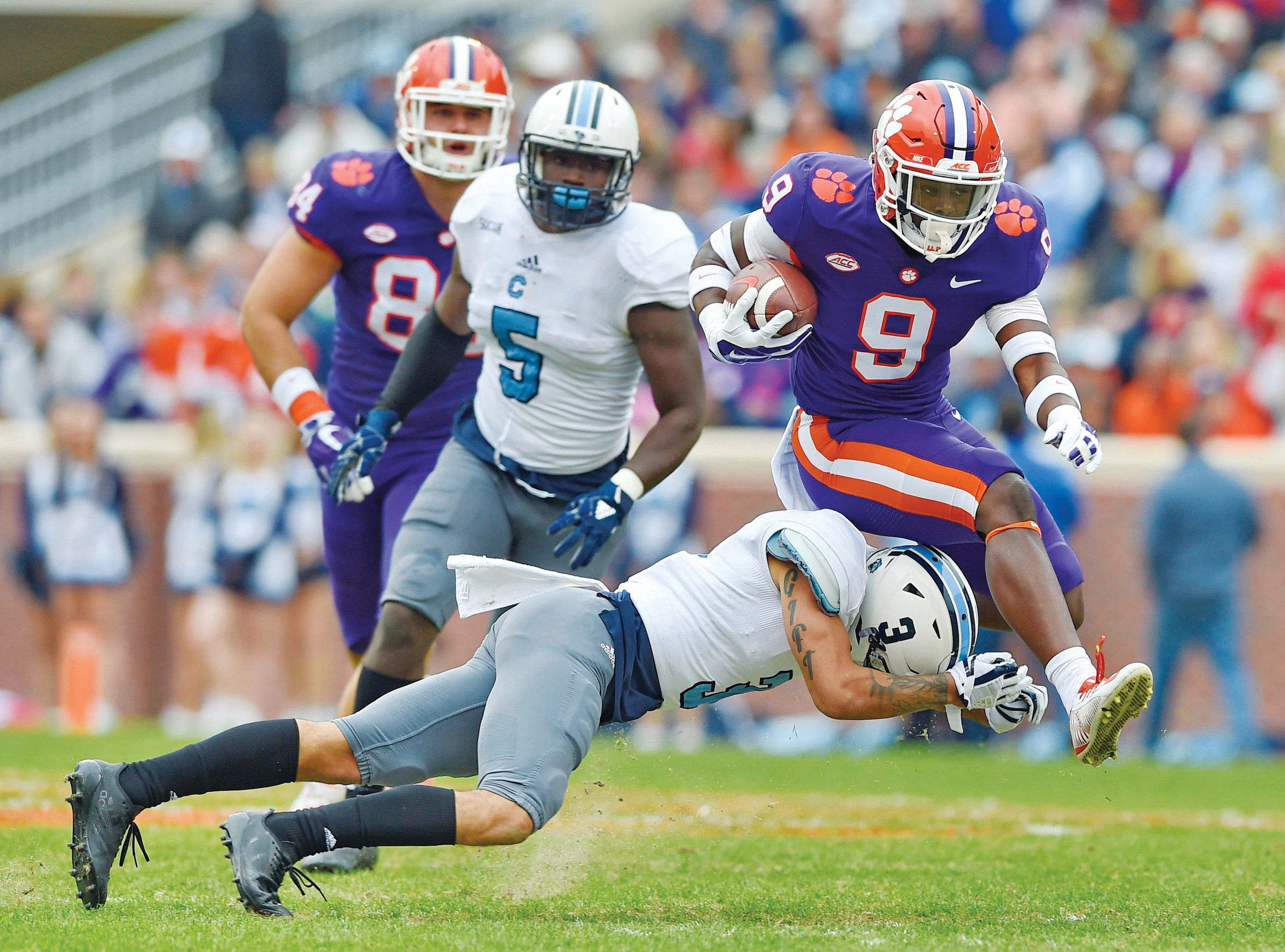 Clemson's Travis Etienne (9) bounds over Citadel's Wally Wilmore to gain a first down during the first half of the Tigers' 61-3 victory over the Bulldogs on Saturday in Clemson.