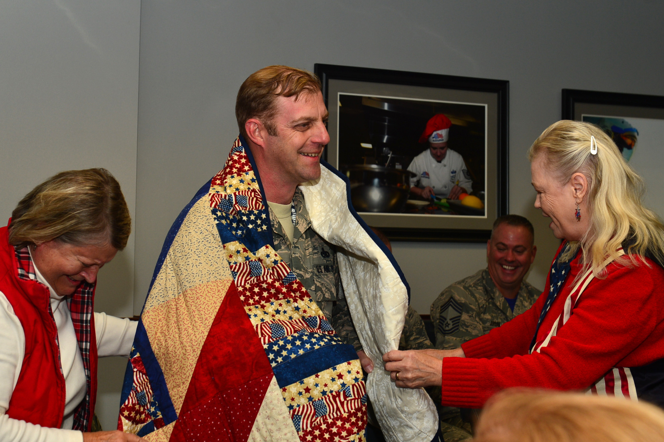 U.S. Air Force Senior Master Sgt. Daniel Henderson, 20th Aircraft Maintenance Squadron, 55th Aircraft Maintenance Unit, assistant superintendent, shares a laugh with Quilts of Valor Foundation members during a QOVF event at Shaw Air Force Base on Nov. 9. Henderson received recognition for his service while deployed overseas and his efforts in preserving the history of the 55th Fighter Squadron while stationed at Shaw.