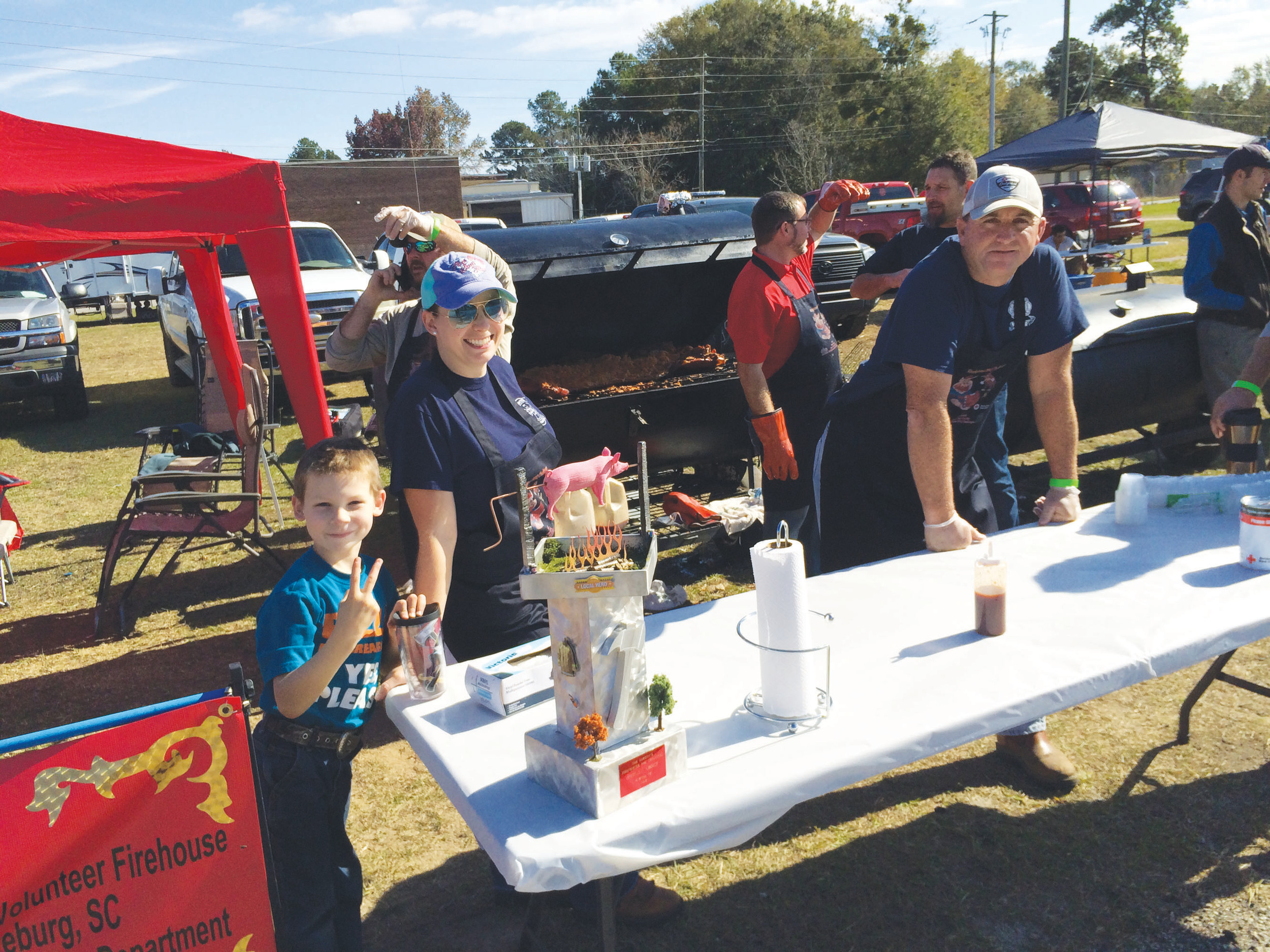 Wyatt Bunyea, 7, has a little fun with his mother, Callie, at Saturday's eighth-annual Capt. Tom Garrity Firefighter BBQ Challenge. Callie said she and her husband, Capt. Aaron Bunyea of Beech Creek FD Station, had been up all night cooking their barbecue for the competition.  Firefighters from 11 stations across South Carolina, Georgia and North Carolina participated in the fundraiser for the Red Cross.