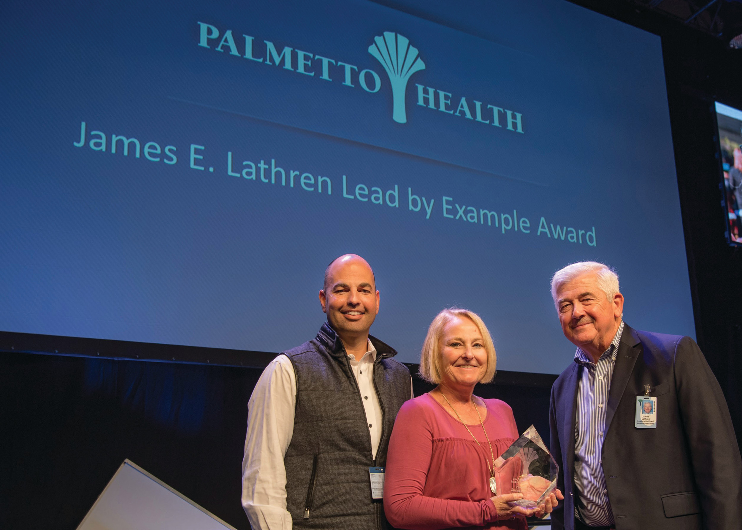"Susan Gaymon receives the James E. Lathren Lead by Example Award from John J. Singerling III, president of Palmetto Health, and James E. ""Jim"" Lathren, for whom the award is named."