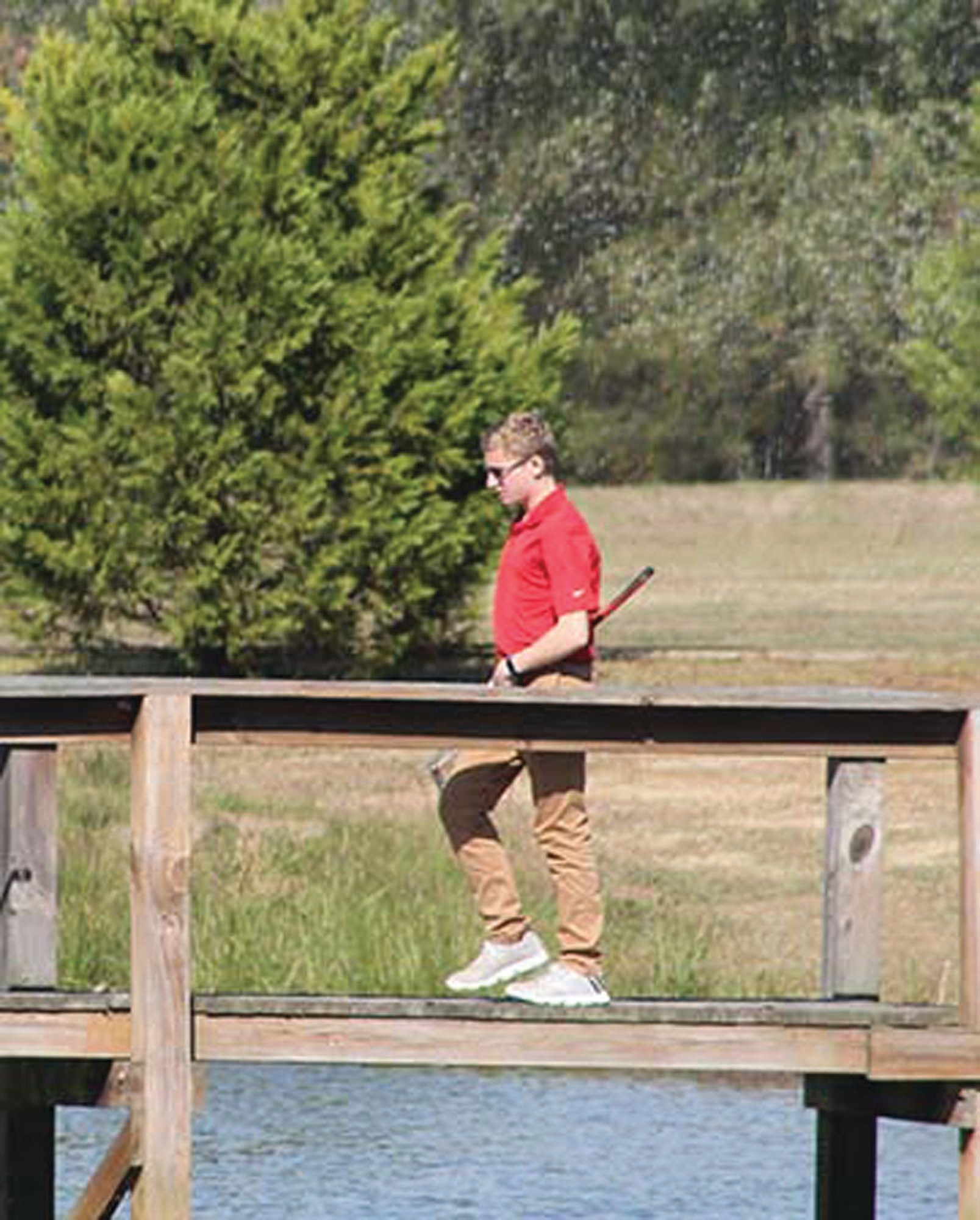 Youth golfer Brice Laney walks over the bridge to the island green at Shannon Greens Golf Course.