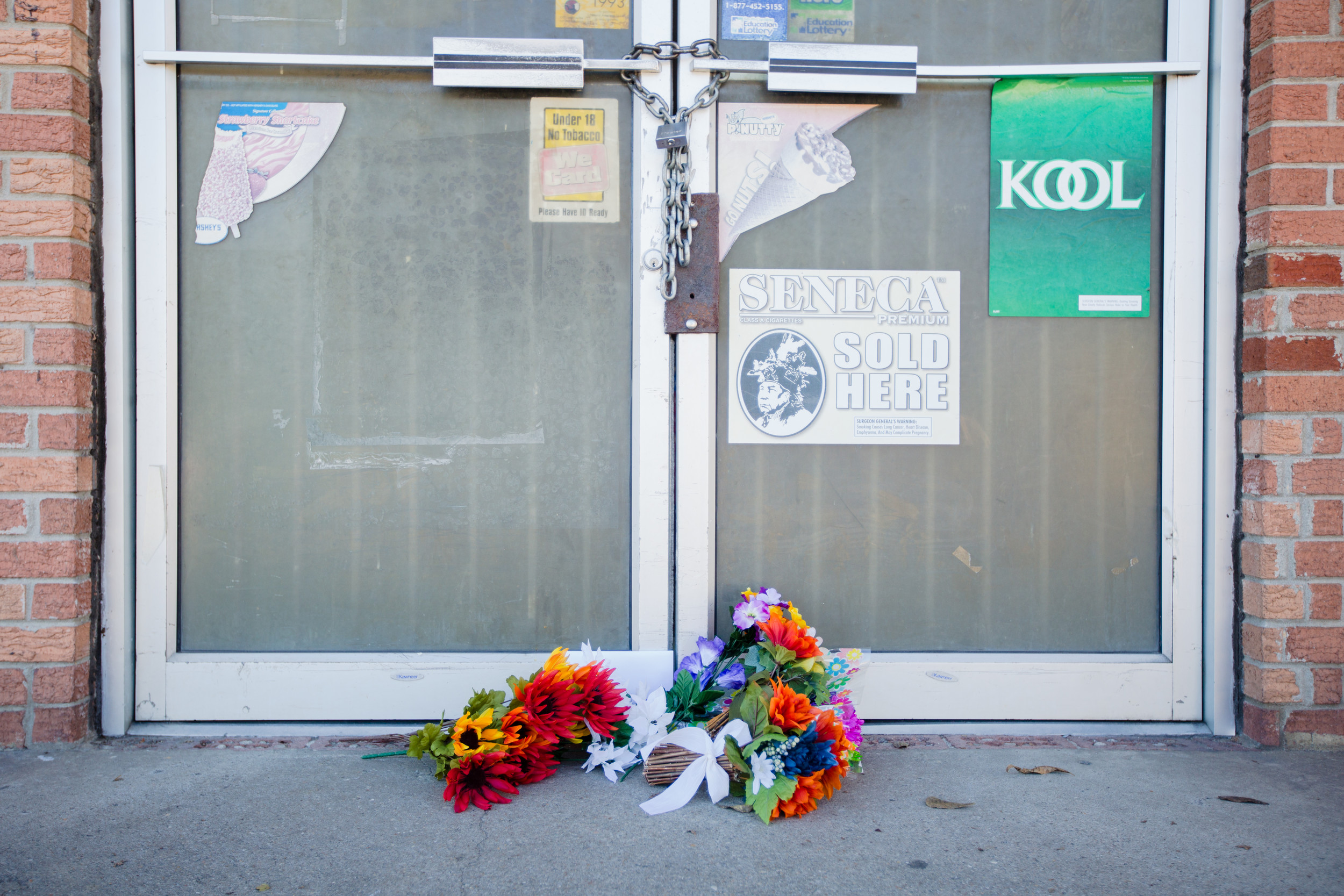 "Flowers rest at the door to Vijaykumar ""Kumar"" Thakorbhai Patel's store on Manning Avenue Monday. Patel was shot to death by two masked men Friday night inside."