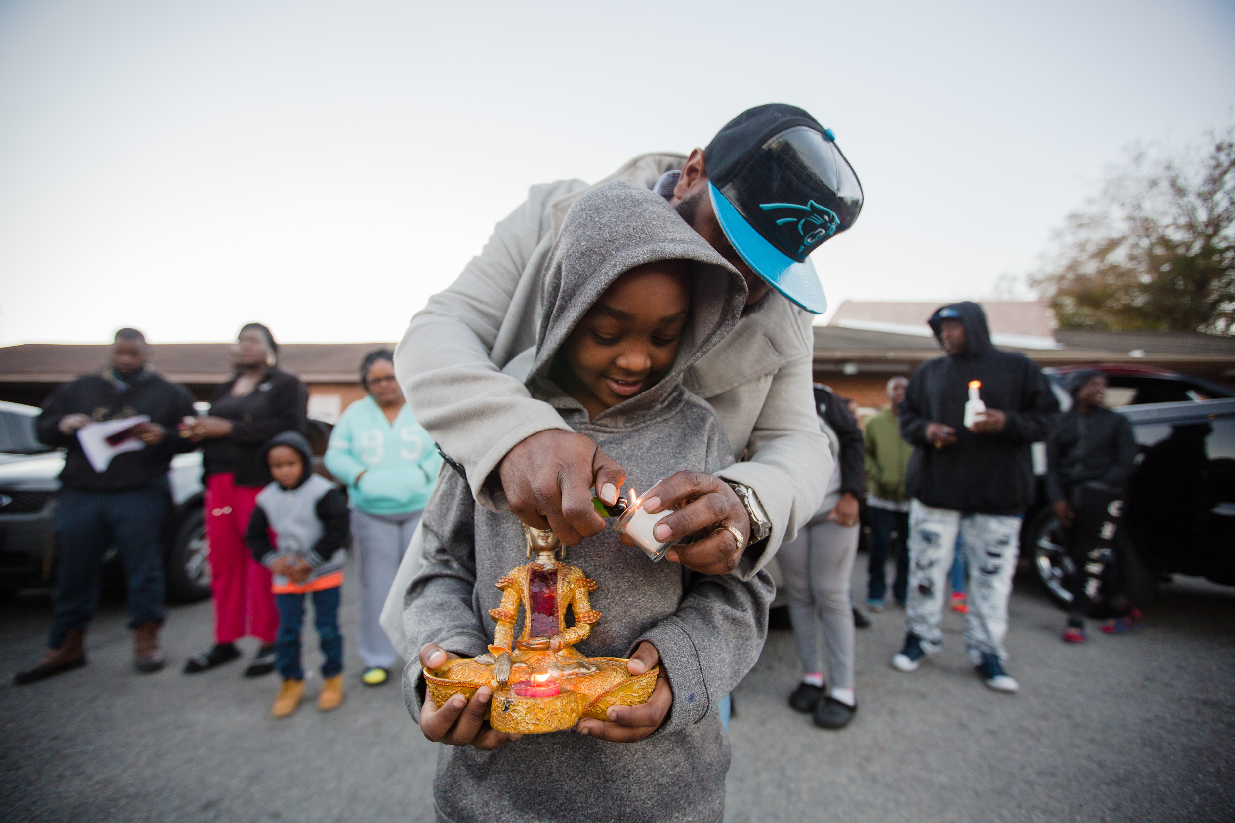 Herbert Benjamin and his son, Dimarion, regulars at the store, hold candles during the vigil. Benjamin and his wife, Sharon, organized the event.