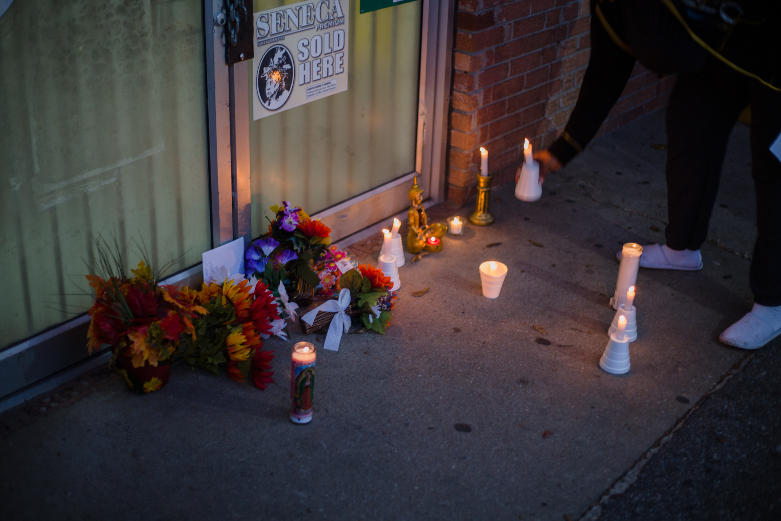 Flowers and candles grow in number outside of the storefront where Patel operated his business for eight years.