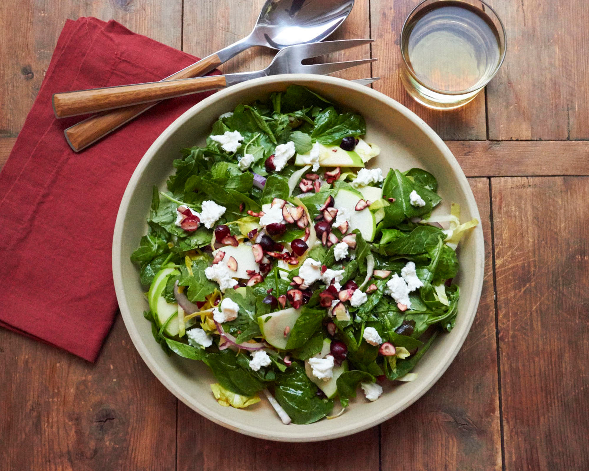 This October 2017 photo shows a winter green salad with cranberries and goat cheese in New York. This salad comes together in 20 minutes, and is a bowl of vibrant color and texture that seems anything but a postscript to the menu.