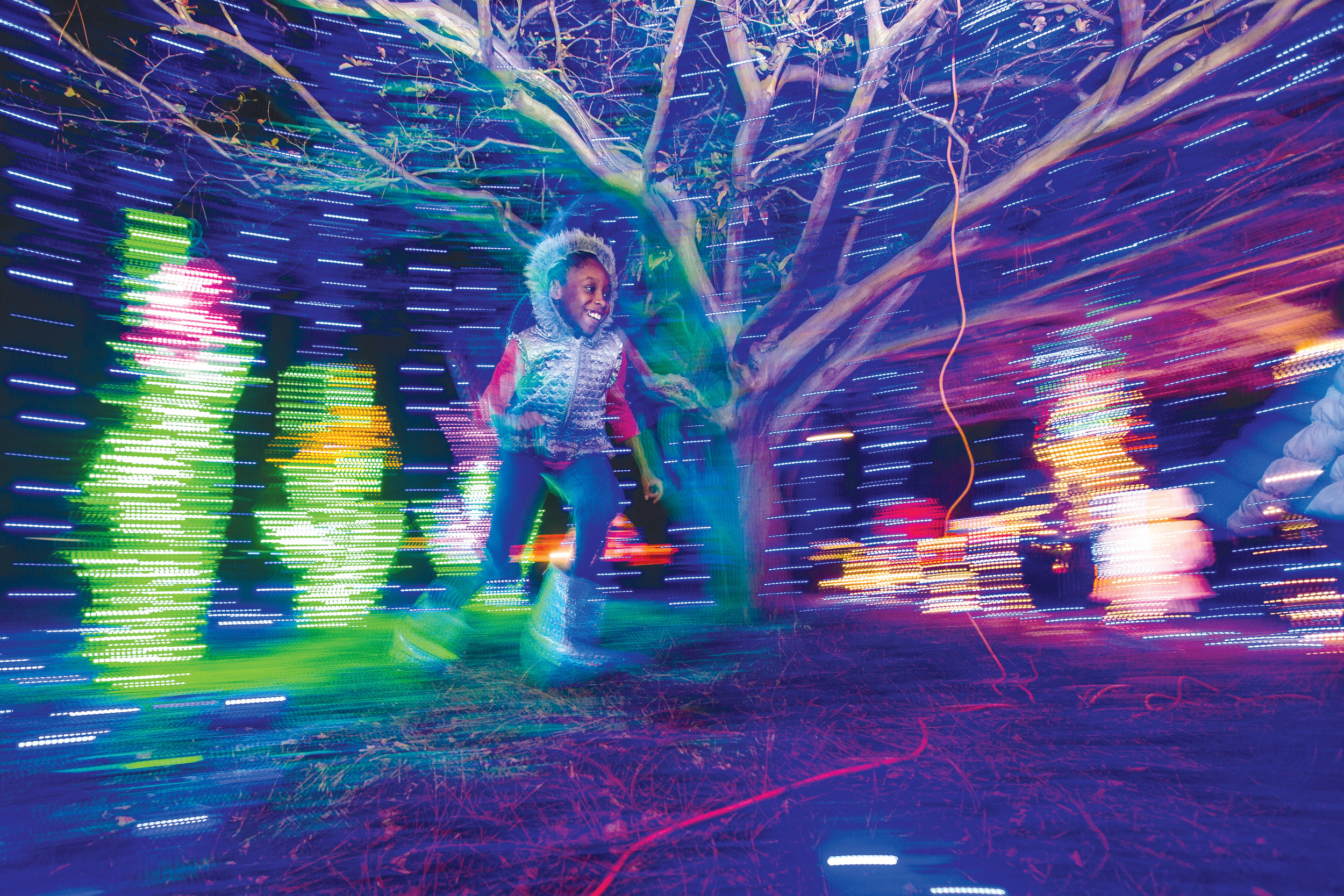 MICAH GREEN / THE SUMTER ITEM Desariyah Walcott runs circles under a tree covered in lights at the 30th-annual Fantasy of Lights kickoff event at Swan Lake-Iris Gardens on Friday.