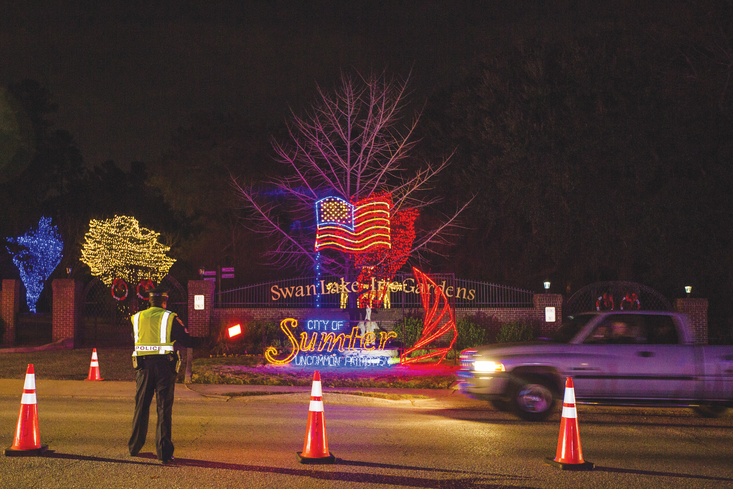 Law enforcement directs traffic at the entrance to Swan Lake-Iris Gardens on Friday.