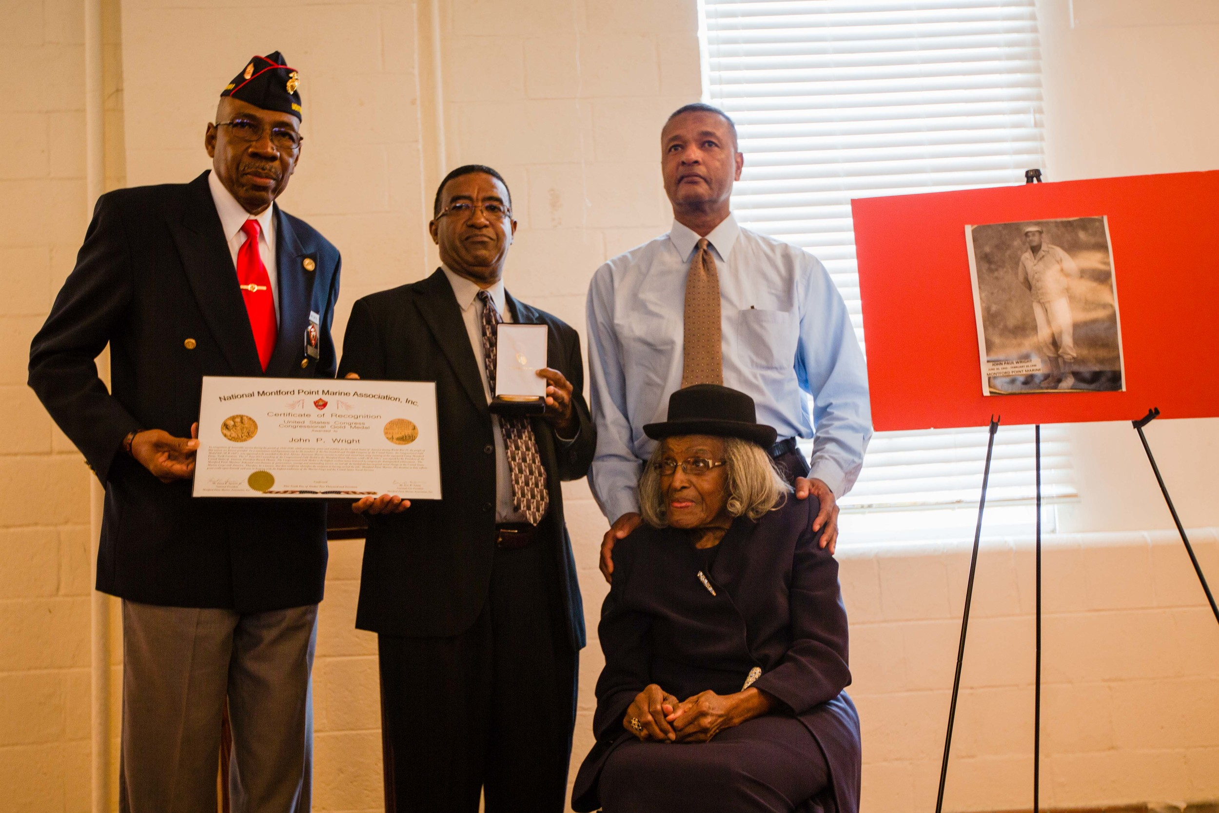 Michael Wright displays the Congressional Gold Medal he accepted on behalf of his late father, John Paul Wright, accompanied, to his right, by Hampton Woodward Jr. and Margaret W. Davis, his father's nephew and sister.