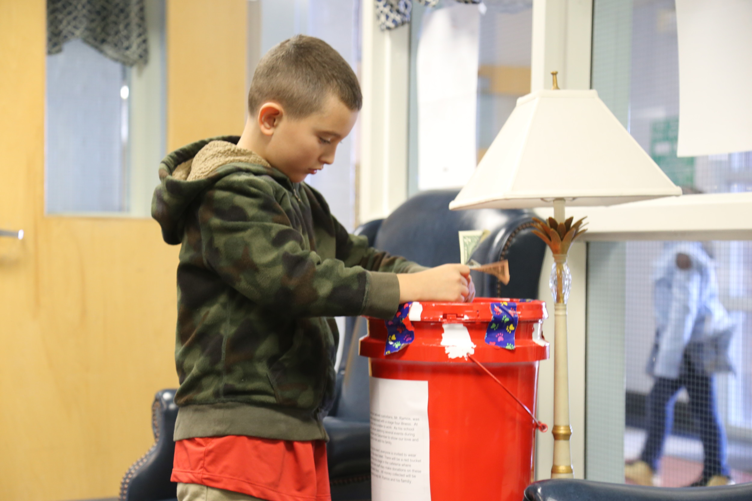 Shaw Heights Elementary School student Federico Murray donates a couple dollars on Tuesday into a bucket at the school designated for offerings to school custodian Daniel Ramos.