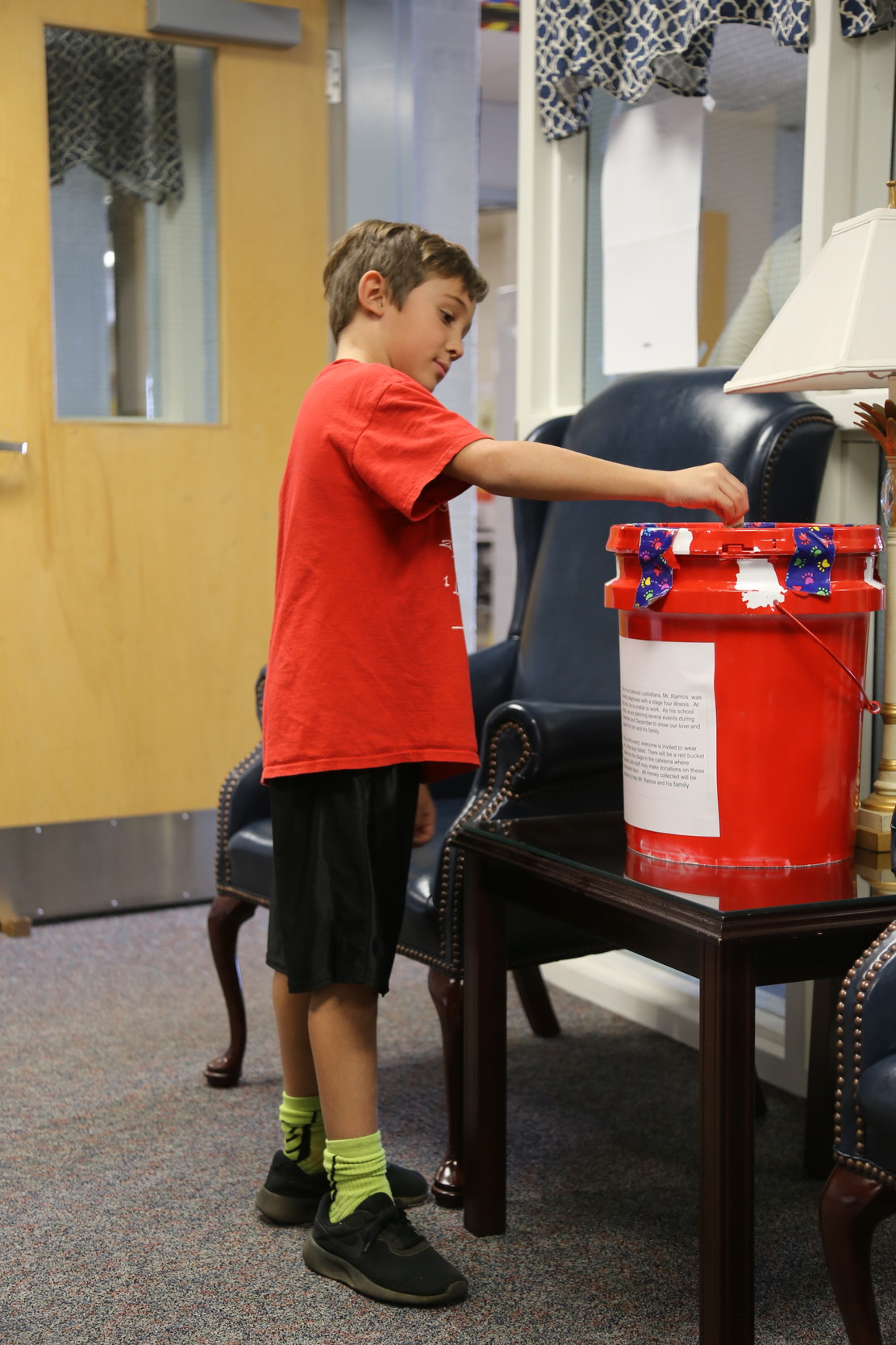 Shaw Heights Elementary School student Ryan Cline donates a dollar bill on Tuesday into a bucket at the school designated for offerings to school custodian Daniel Ramos.