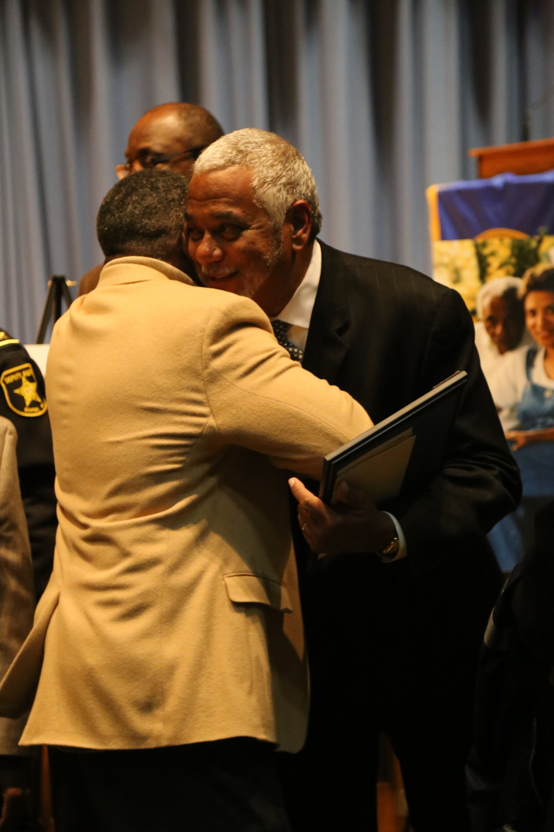 "Ernest ""Chip"" Finney III, son of retired chief justice Ernest A. Finney Jr., hugs a visitor during a public visitation service for his father at Morris College."