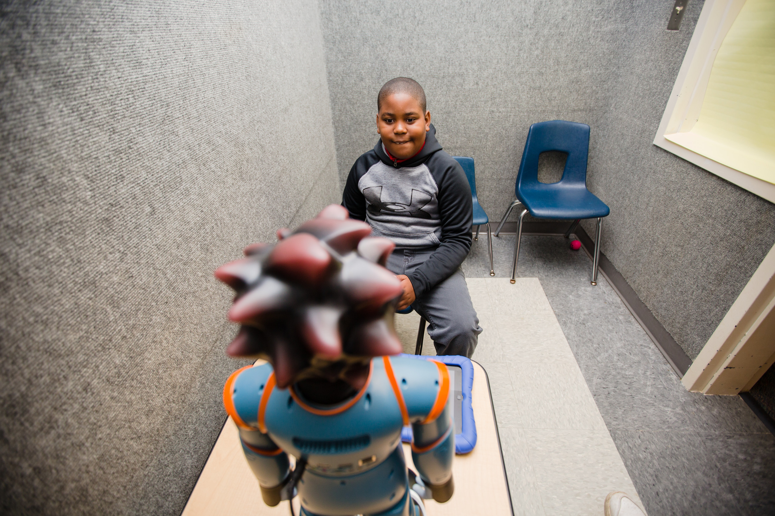 Devon Lester, 9, interacts with Milo in an isolation room at Kingsbury Elementary.