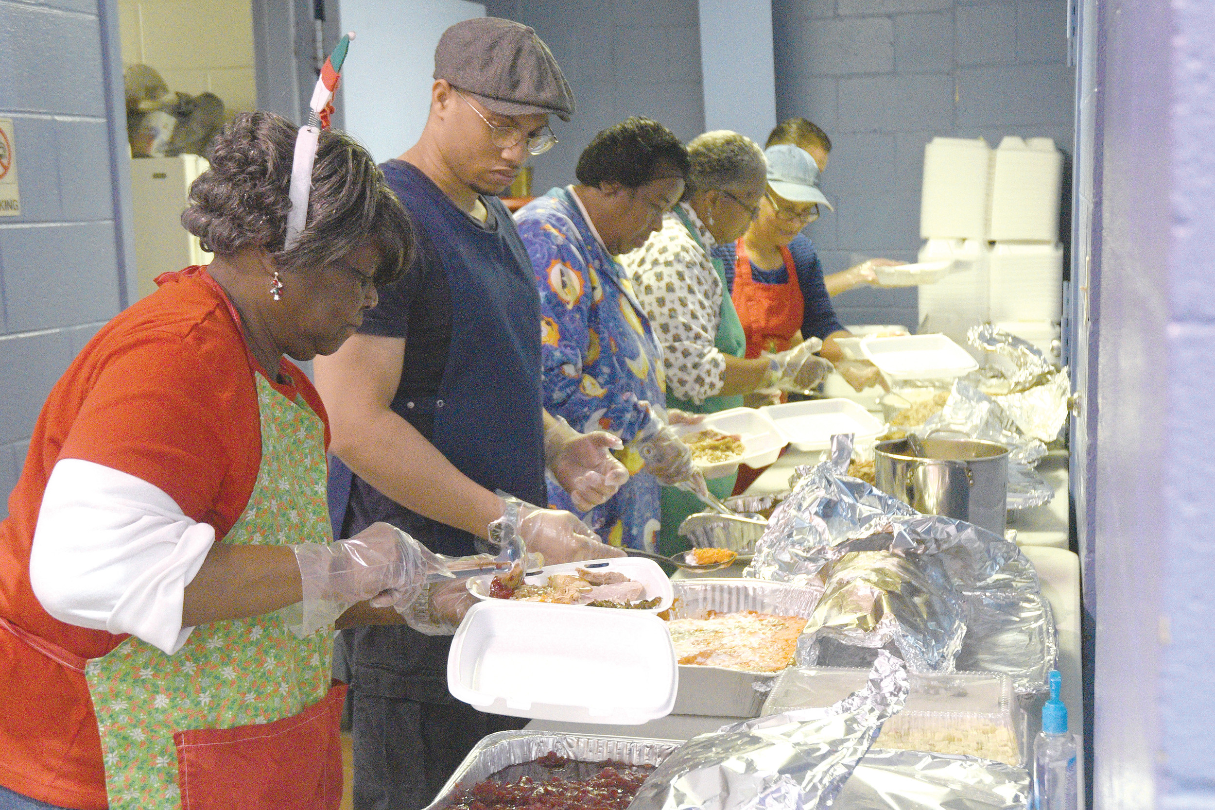 Geraldine Singleton adds cranberry sauce on the assembly line of packaged meals during the annual Christmas dinner served in 2015 in the South Sumter Park gymnasium.
