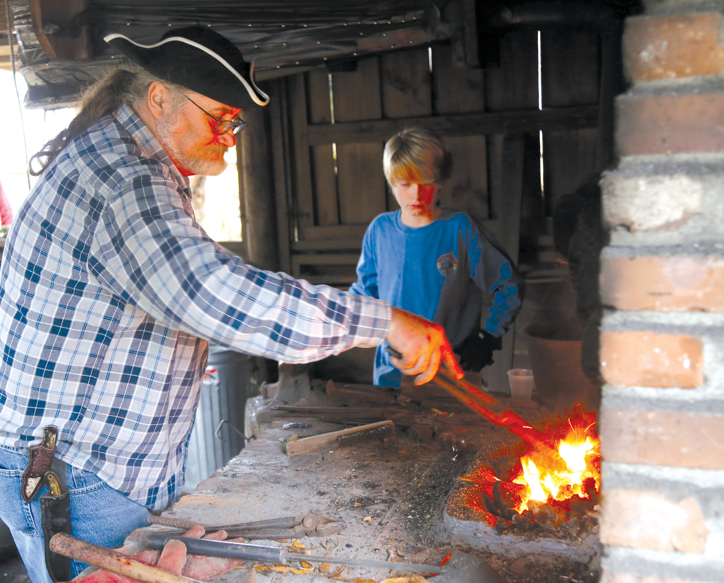 Blacksmith Randall Draper, left, shows Asher Hasbrouck how knifes were made 200 years ago on Saturday at the Carolina Backcountry Christmas re-enactment at the Sumter County Museum.