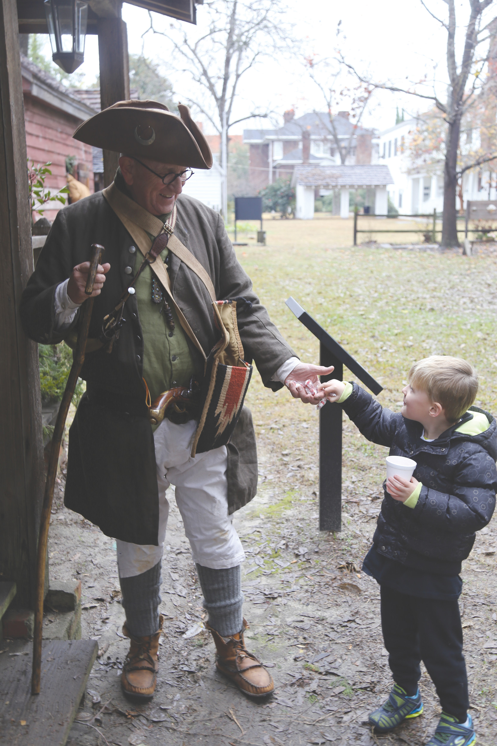Ryan Heim, 5, takes a piece of candy from Frank Holloway, dressed as a Revolutionary War militiaman, at the event.