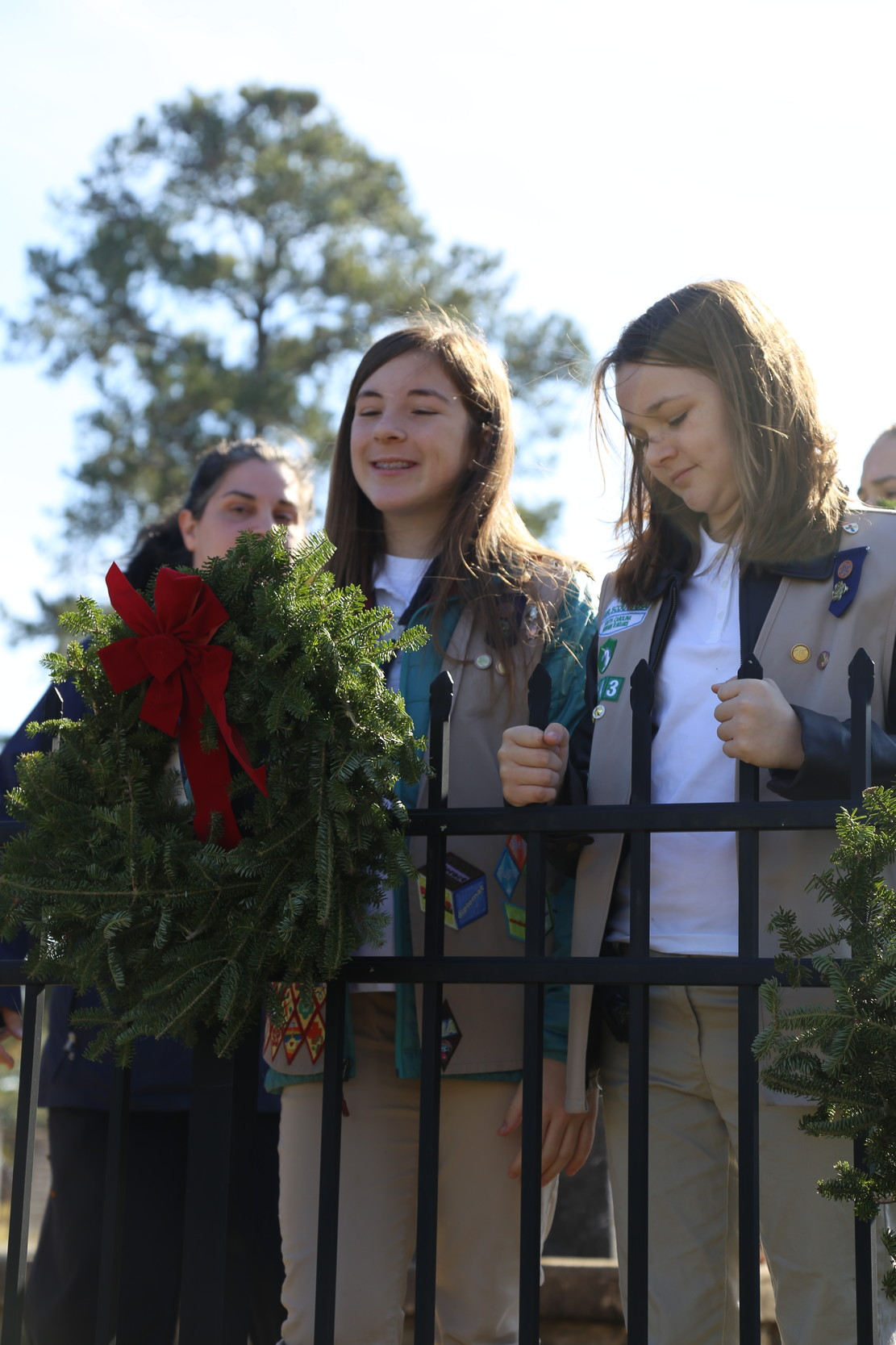 A member of a Girl Scout troop places a wreath on the fence of Sumter Cemetery.