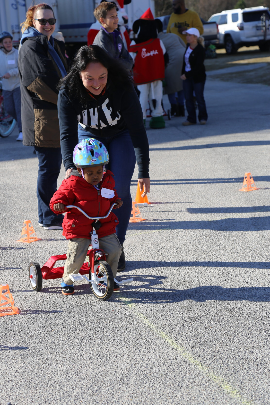 PHOTOS BY ADRIENNE SARVIS / THE SUMTER ITEMA child learns to ride a tricycle at the Cycles for Christmas giveaway on Saturday organized by Evening Optimist Club of Sumter.