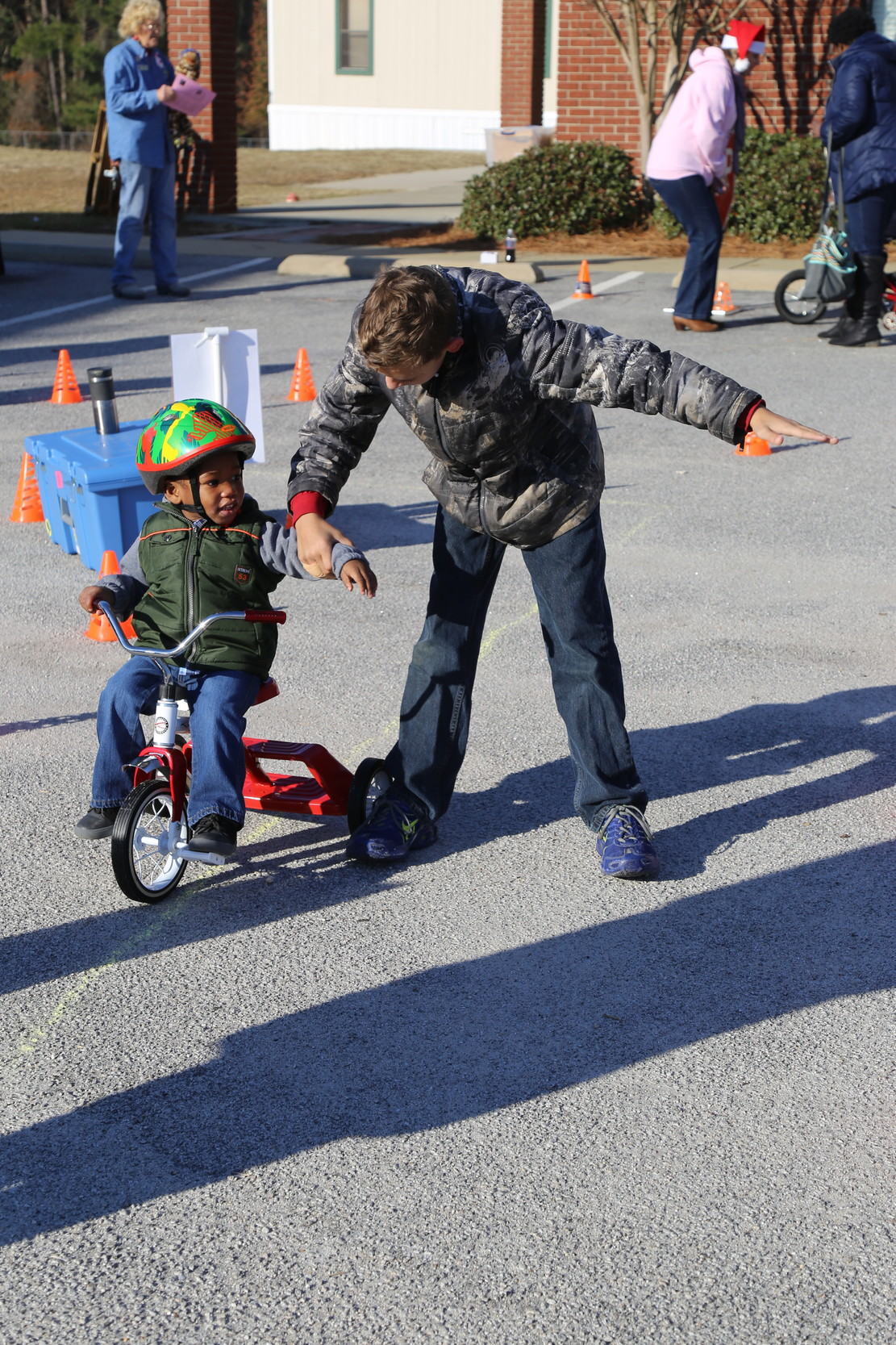 Children learn proper hand signals while riding their bikes at  Saturday's giveaway.