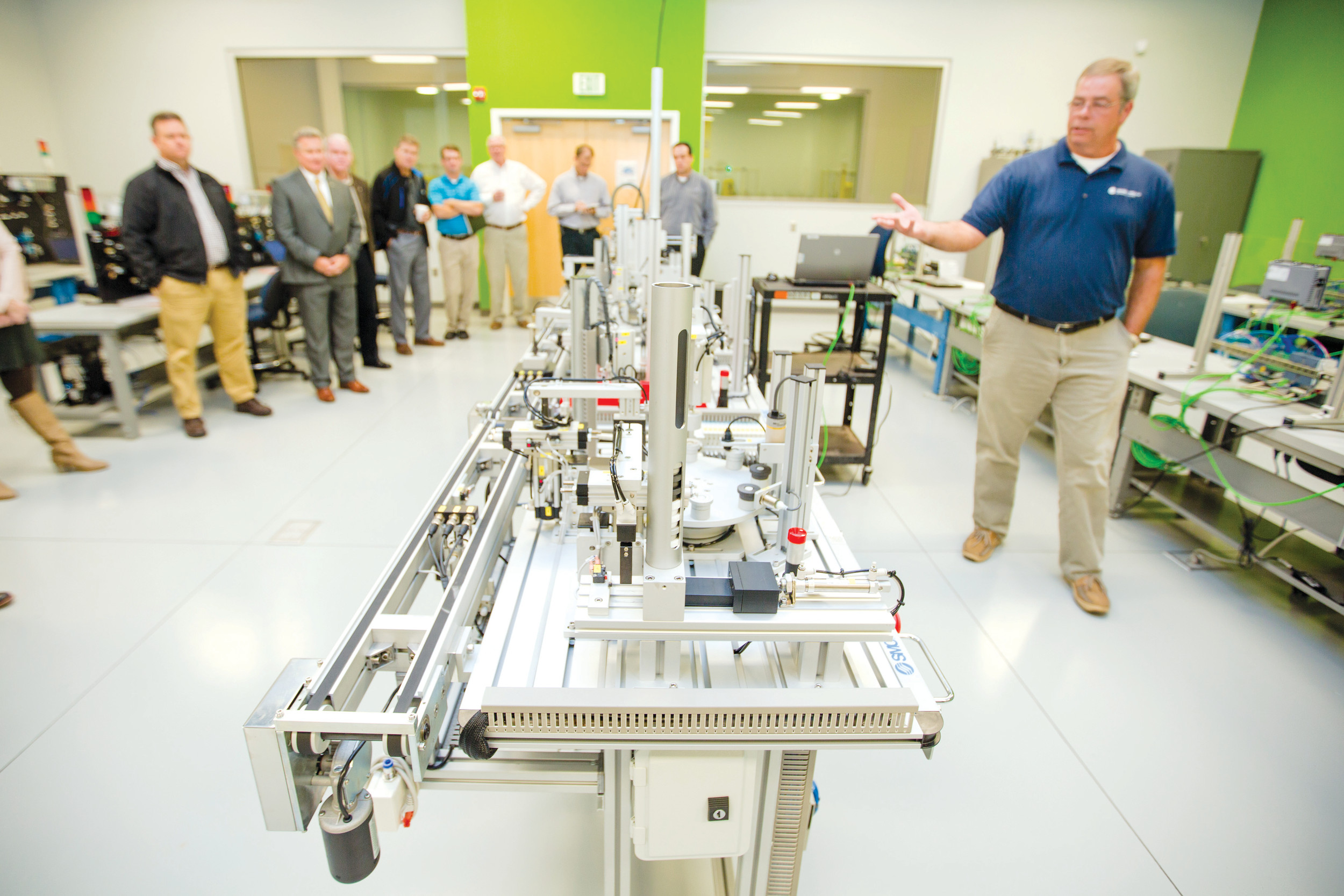 Bert Hancock, academic program manager for Mechatronics at Central Carolina Technical College, shows off the college's new four-stage, flexible manufacturing system recently to industrial and community leaders.