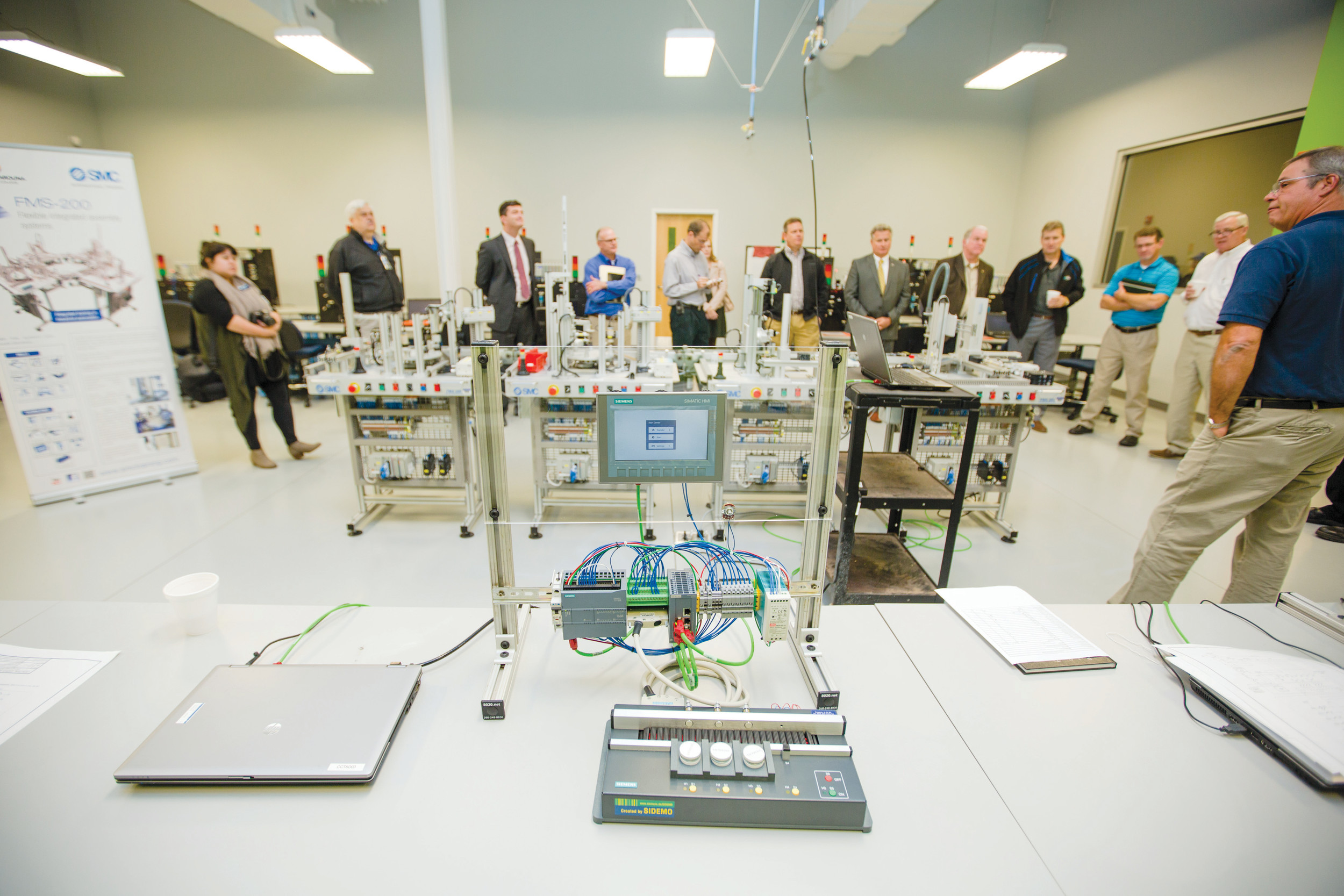 Bert Hancock, academic program manager for Mechatronics at Central Carolina Technical College, shows off the college's new four-stage flexible manufacturing system recently to industrial and community leaders.