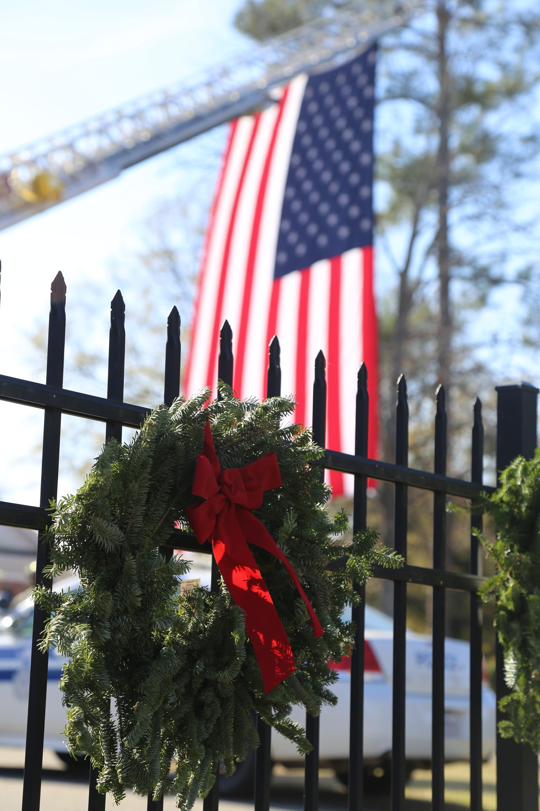 A wreath hangs from the fence at Sumter Cemetery after being placed by members of local Scout troops and Civil Air Patrol members on Saturday. See more photos from the event on page A5.
