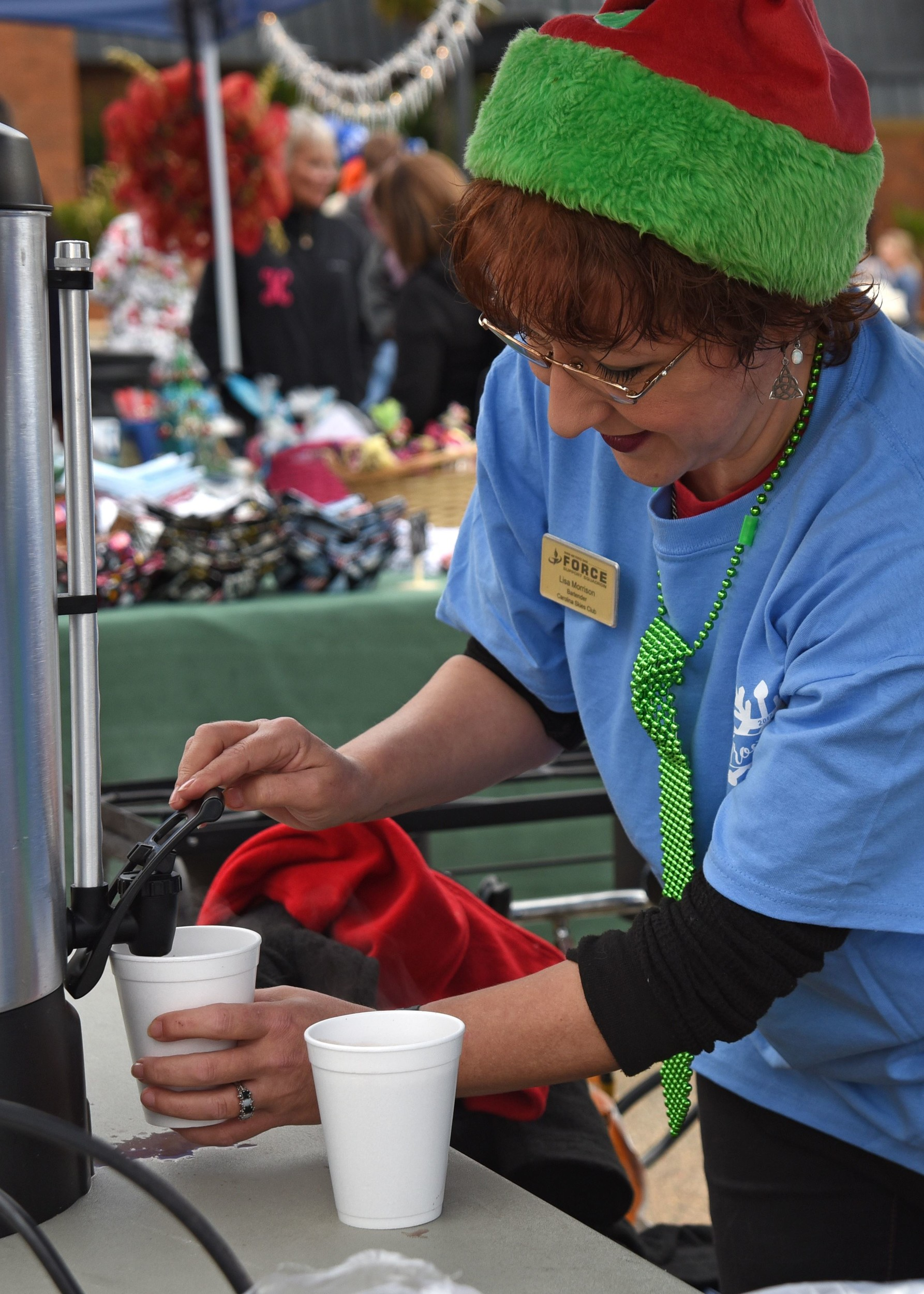Lisa Morrison, 20th Force Support Squadron employee, prepares a drink for a guest at Frosty Fest, a family-friendly winter celebration at Shaw Air Force Base. Approximately 4,500 Team Shaw members gathered to eat, play, shop and celebrate the season.
