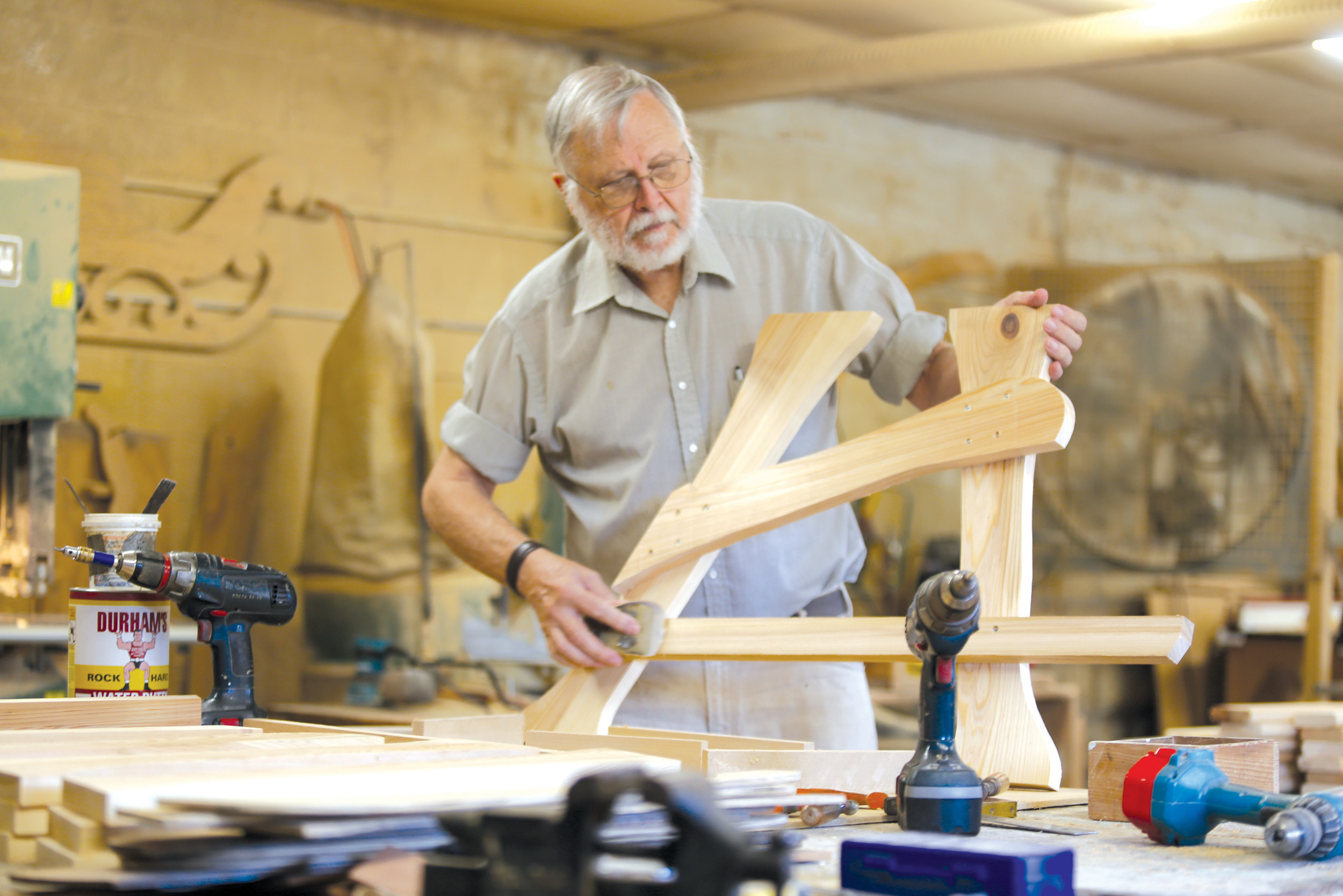 BRUCE MILLS / THE SUMTER ITEMDick Dabbs sands the legs to a chair at Crossroads Workshop recently. Dabbs constructs and sells mostly swings, rockers and Adirondack chairs at his Mayesville business.