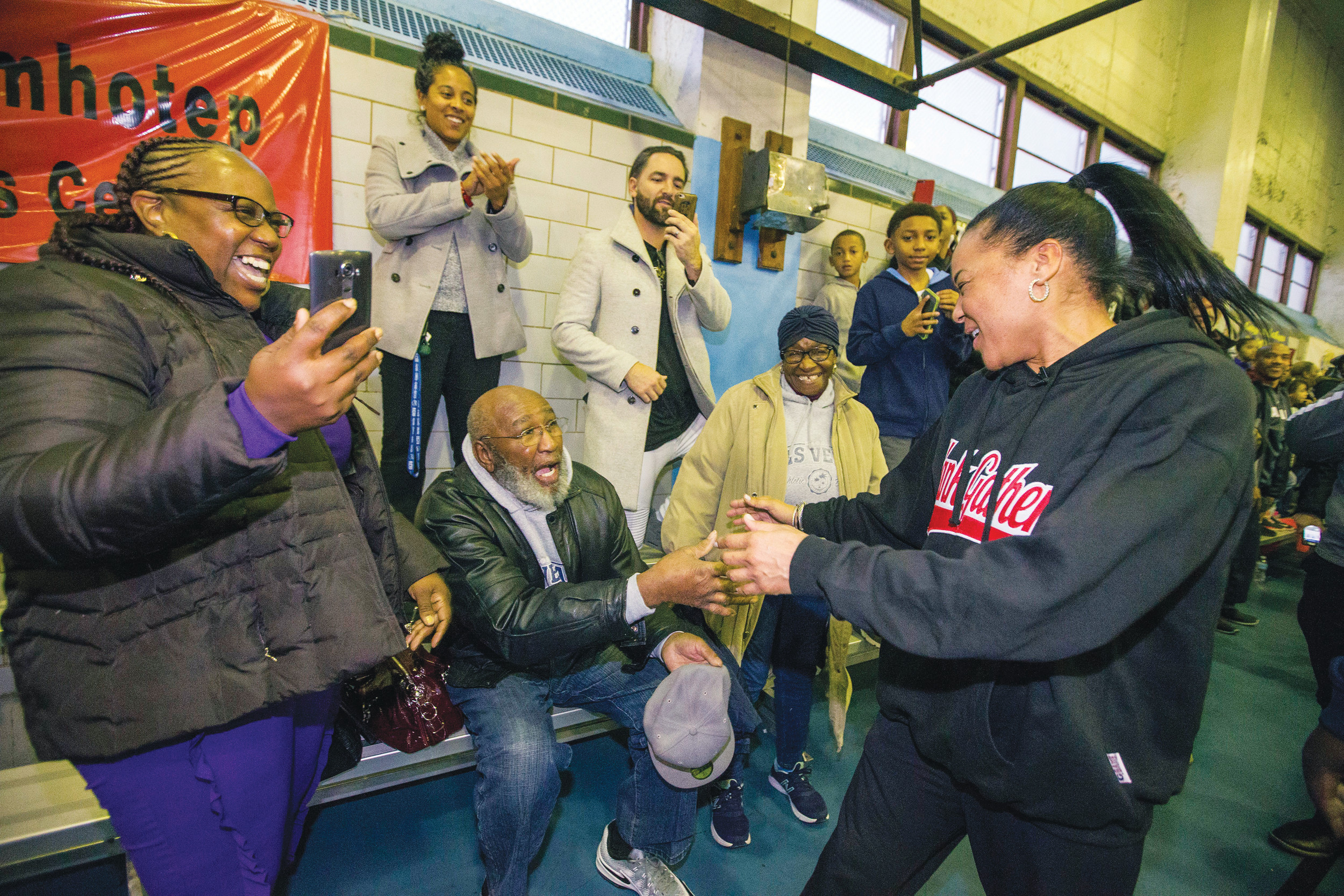 Dawn Staley, right, is greeted by neighborhood friends as Dawn Staley Day is celebrated on Dec. 20 at the Hank Gathers Recreation Center in Philadelphia.