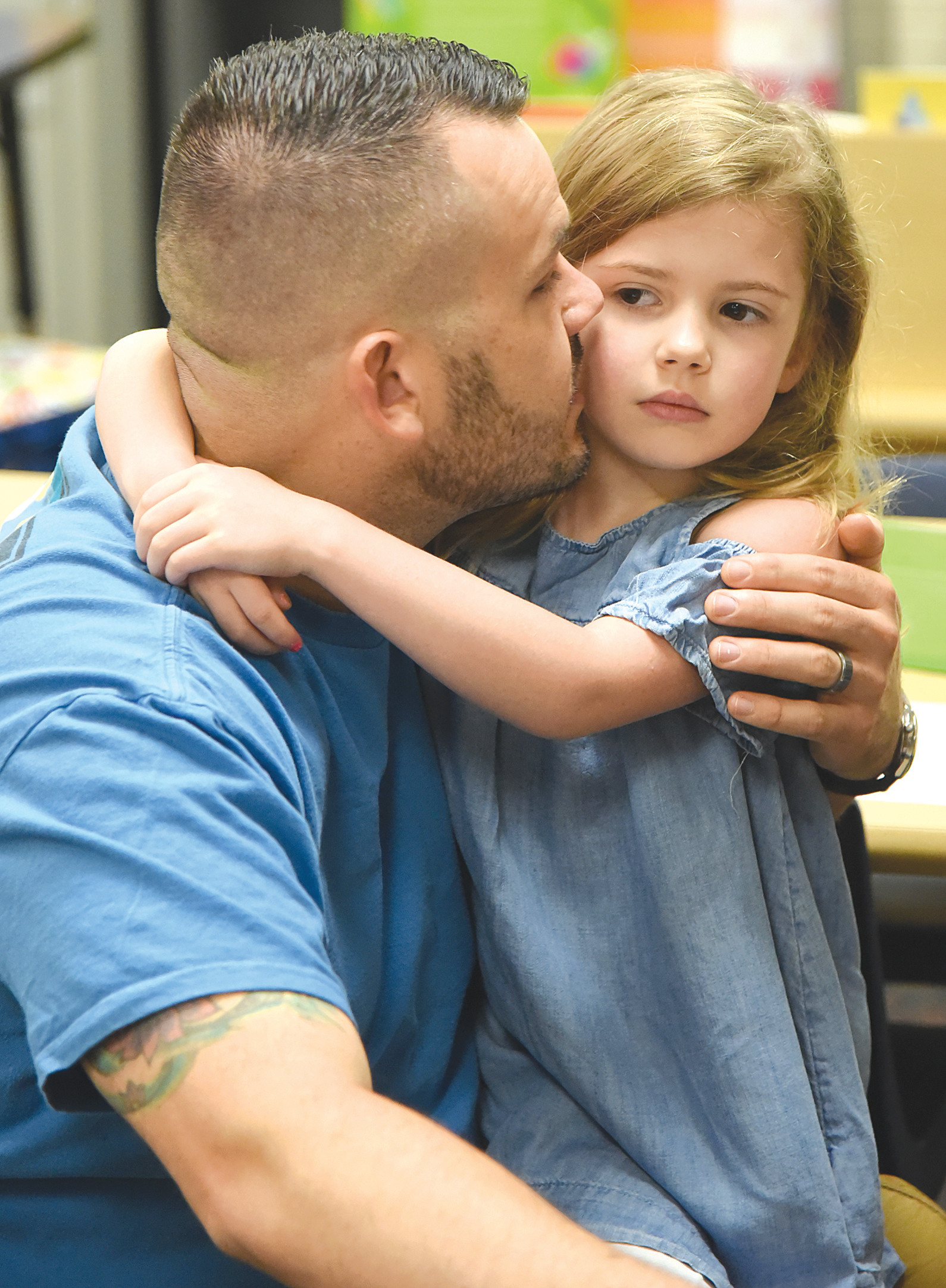 U.S. Air Force Master Sgt. Jeff Zell gives his daughter, Eva, 5, a kiss before leaving her in a kindergarten class on the first day of school at Alice Drive Elementary School.
