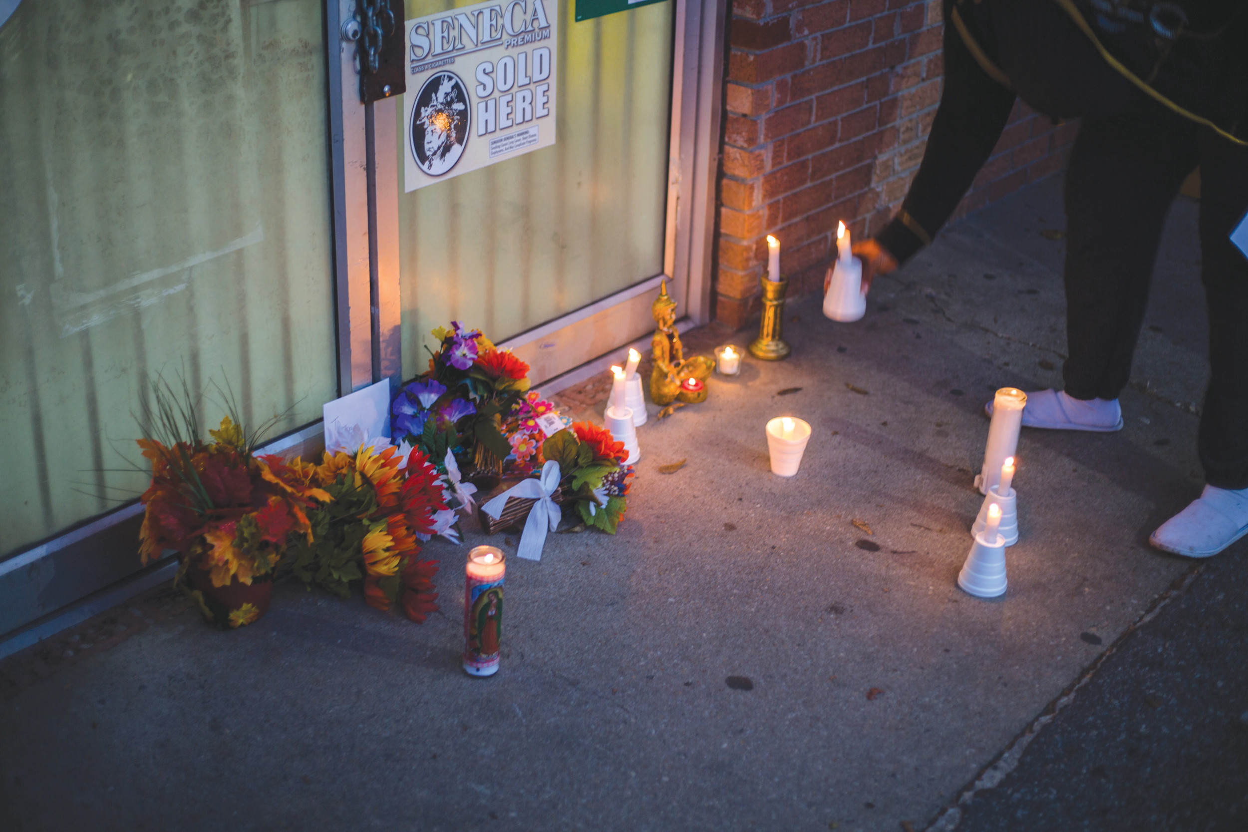 Flowers and candles are seen outside of the storefront of Save-Mart Grocery during a vigil for Vijaykumar Patel, who was shot and killed in his store on Nov. 24.