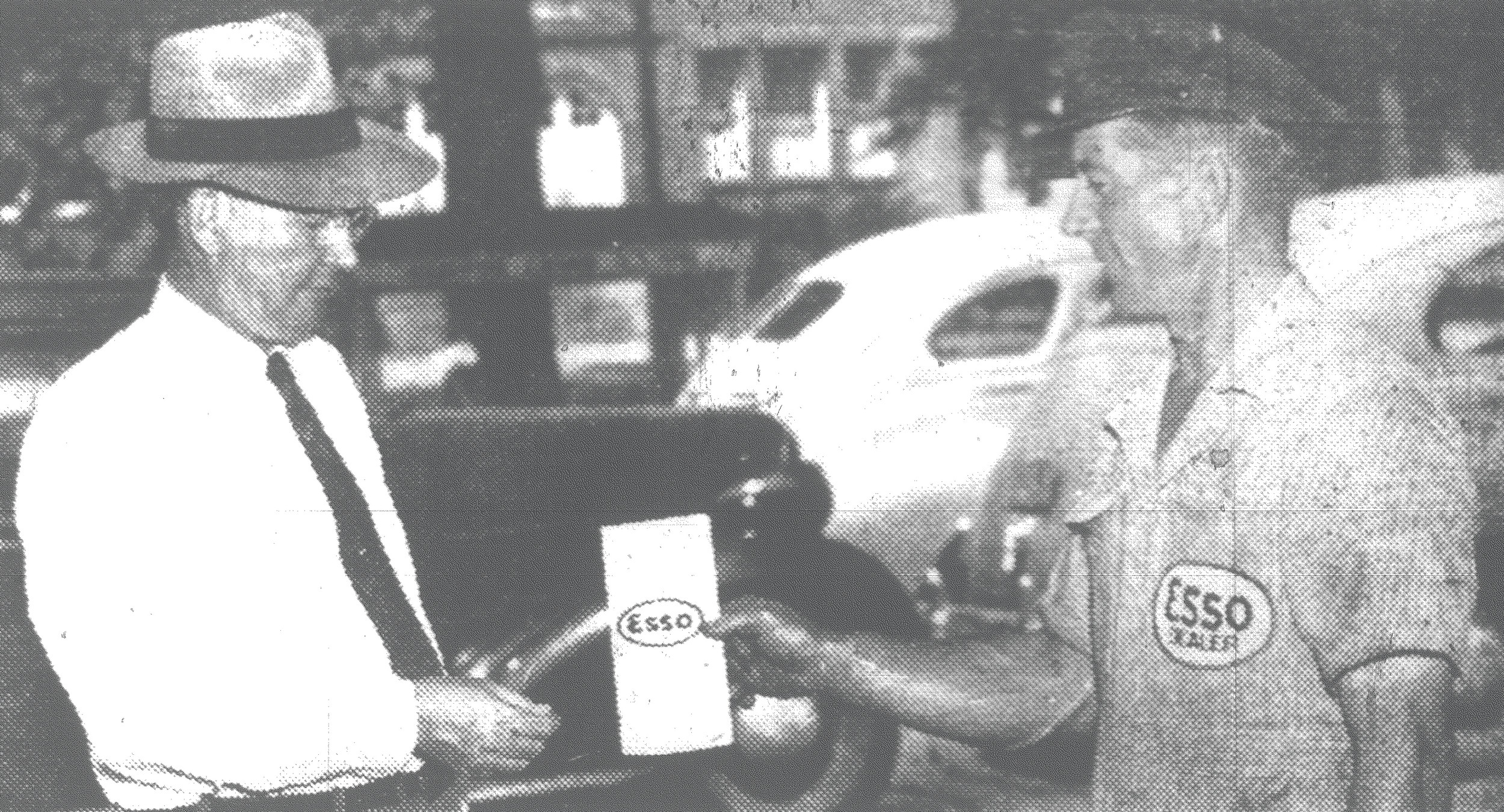 Mayor F.B. Creech receives an Esso Victory Home Canning Guide and Time Table from Phillip DuBose at the Esso service station, corner of Liberty and Washington streets, in 1943. Esso Marketers printed and distributed these time guides to aid the war effort.
