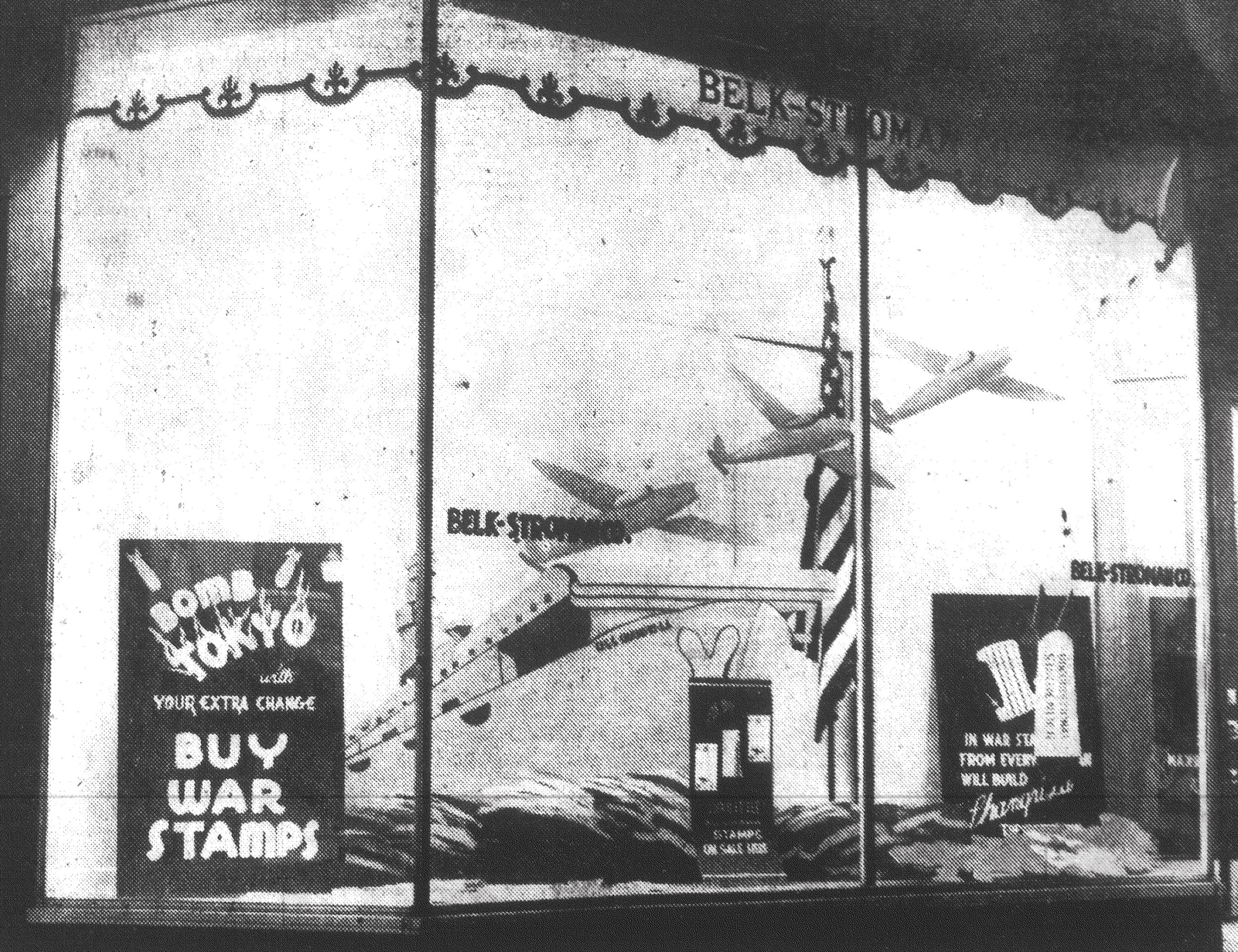 """Buy stamps to bomb Tokyo"" from the Aircraft Carrier Shang ri-la is the aim of a window display at Belk-Stroman Co. The display was blue and was fixed by J.O. Talbort, employee of the store, in 1943."