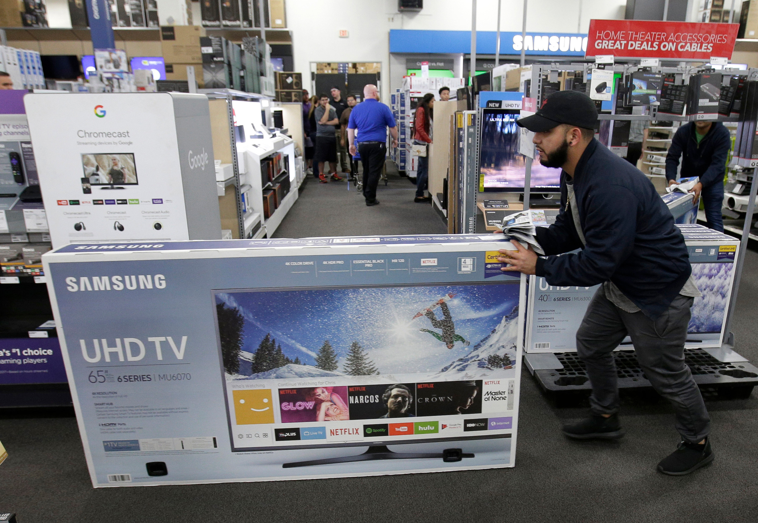 jesus reyes pushes a tv down an aisle as he shops a black friday sale at - Best Buy Day After Christmas Sale