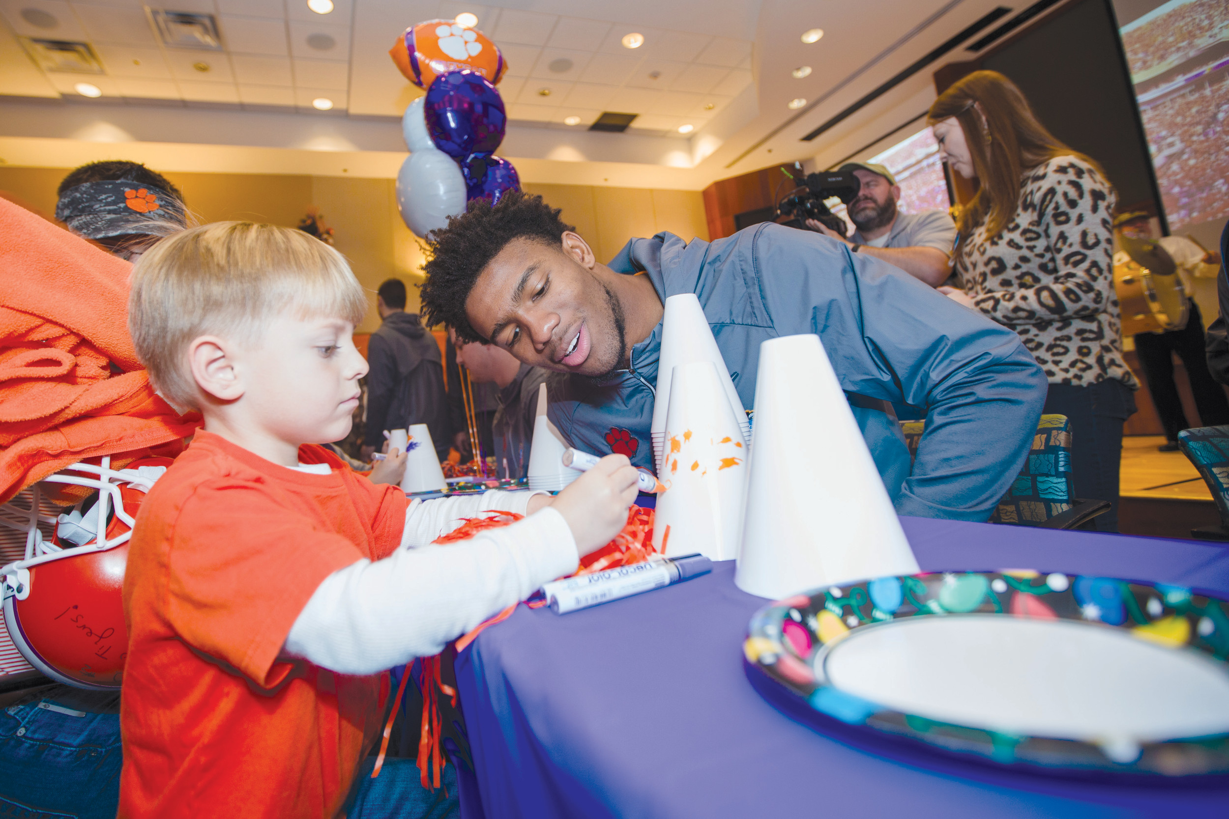 Clemson quarterback Kelly Bryant helps a patient at the hospital decorate a megaphone at the party Saturday.