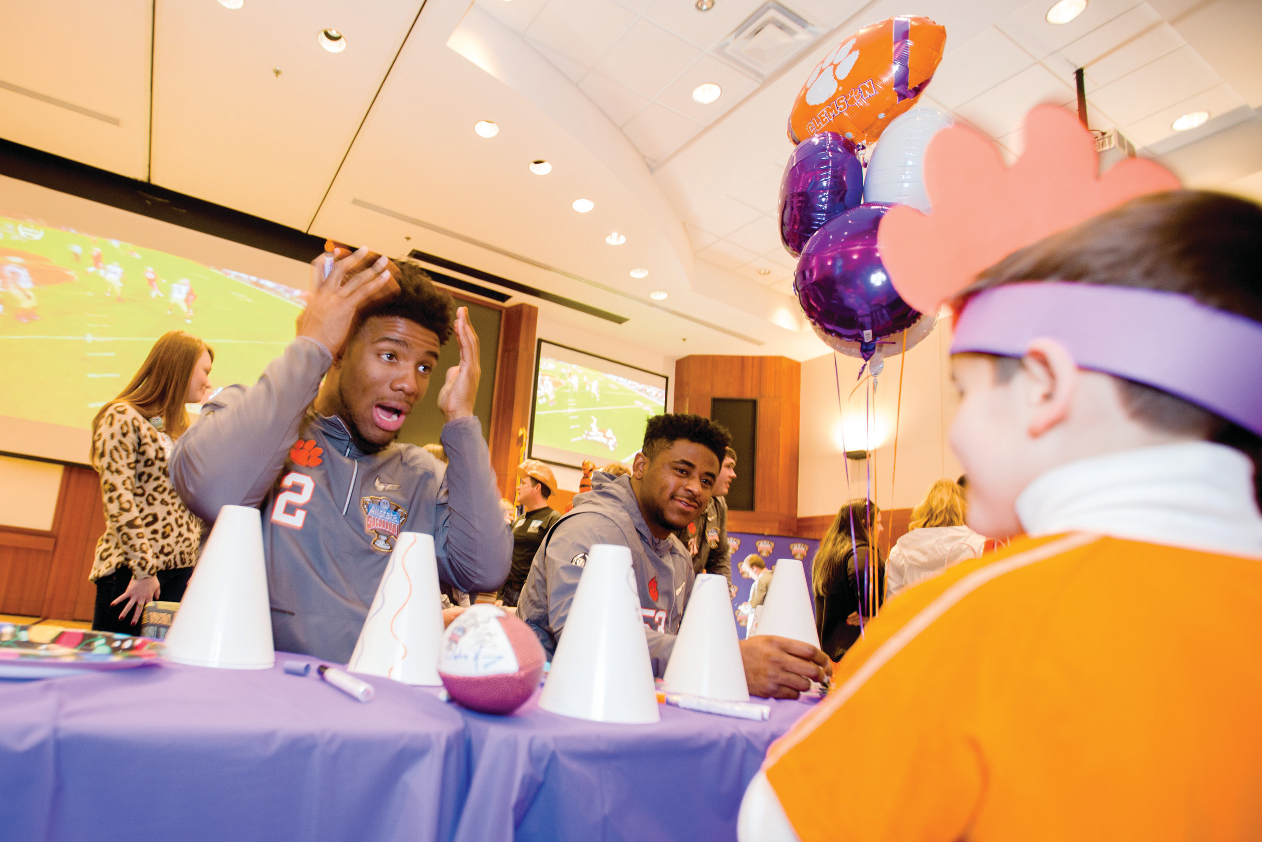 Clemson quarterback Kelly Bryant plays around with a patient of Ochsner Baptist Children's Hospital while he decorates a megaphone at a party thrown on Saturday for the patients and their families in New Orleans.