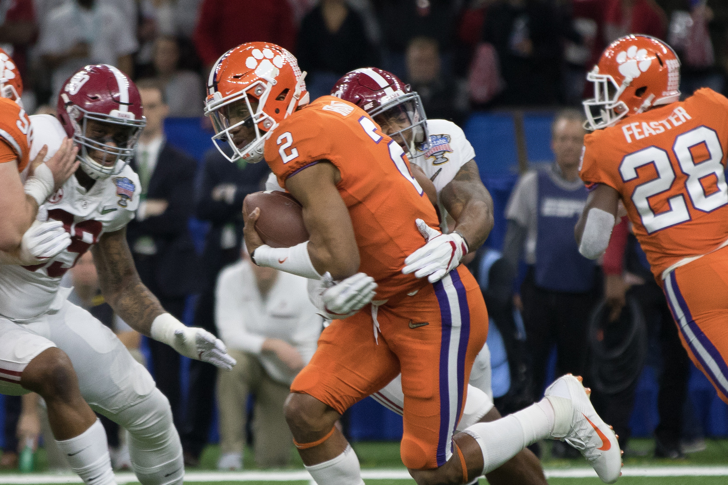Clemson quarterback Kelly Bryant gets wrapped up by an Alabama defender.