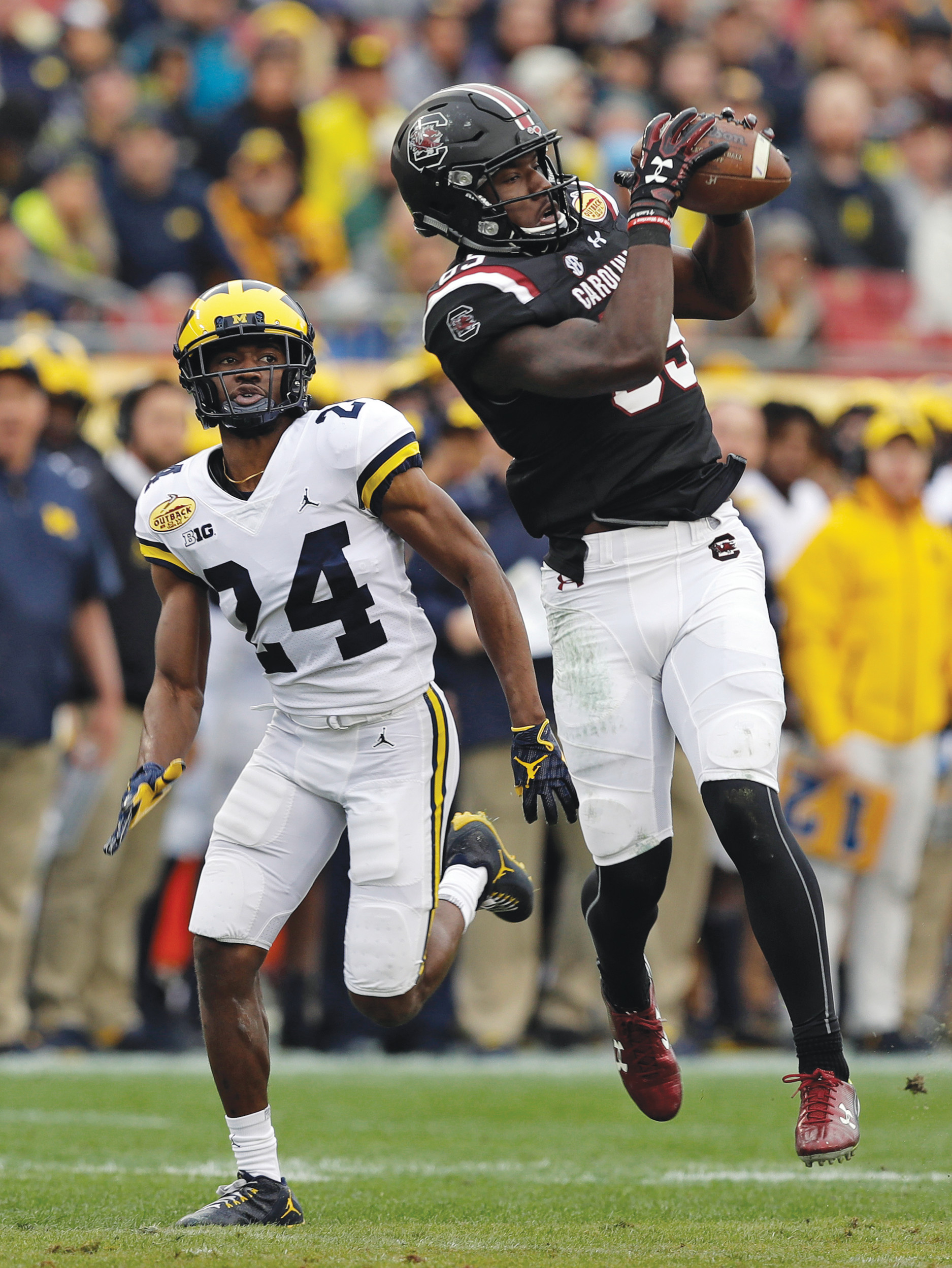South Carolina wide receiver Bryan Edwards (89) pulls in a pass in front of Michigan defensive back Lavert Hill (24) during the Gamecocks' 26-19 victory in the Outback Bowl on Monday in Tampa, Florida.