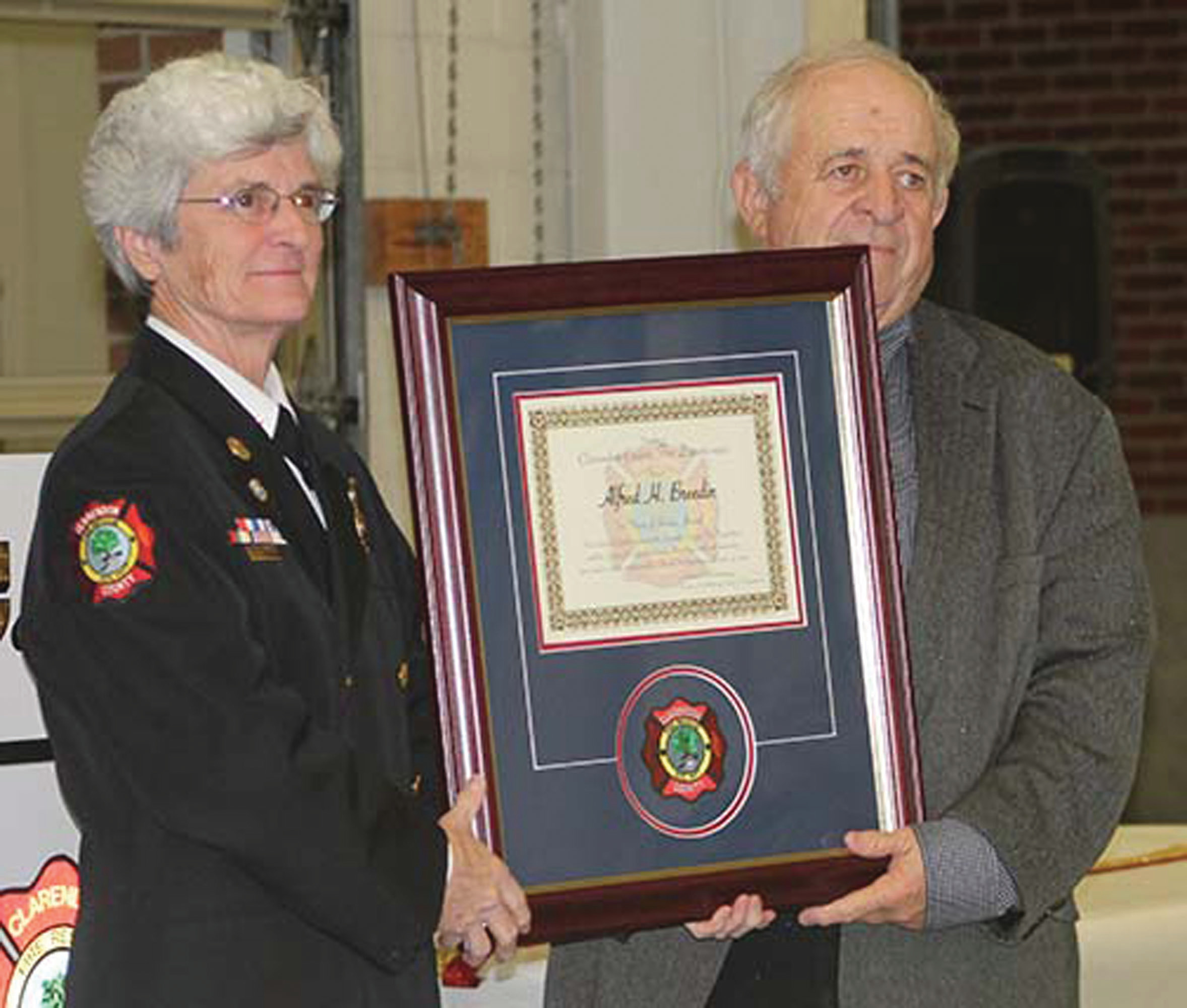 Volunteer firefighter Alfred Breedin receives a plaque from Fire Chief Frances Richbourg for recognition for his 40 years of service to Clarendon County Fire Department at the department's annual awards and Christmas dinner.