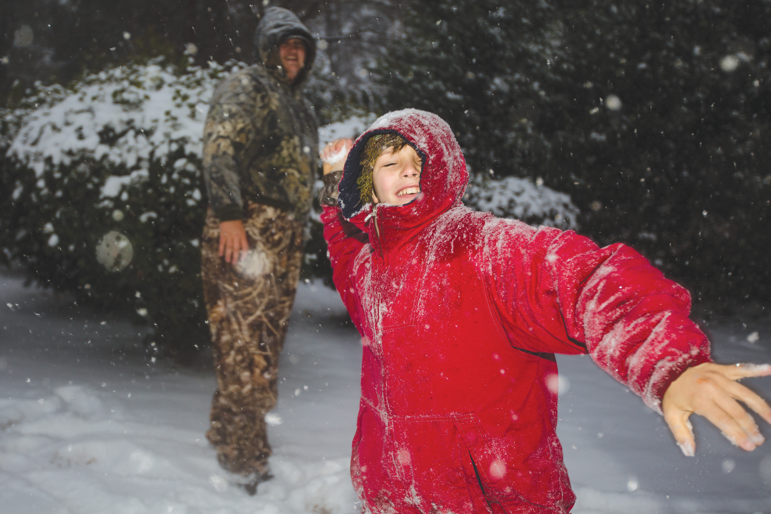 Emmitt Bilton throws snowballs in a front yard on Riley Street in Sumter on Wednesday afternoon.