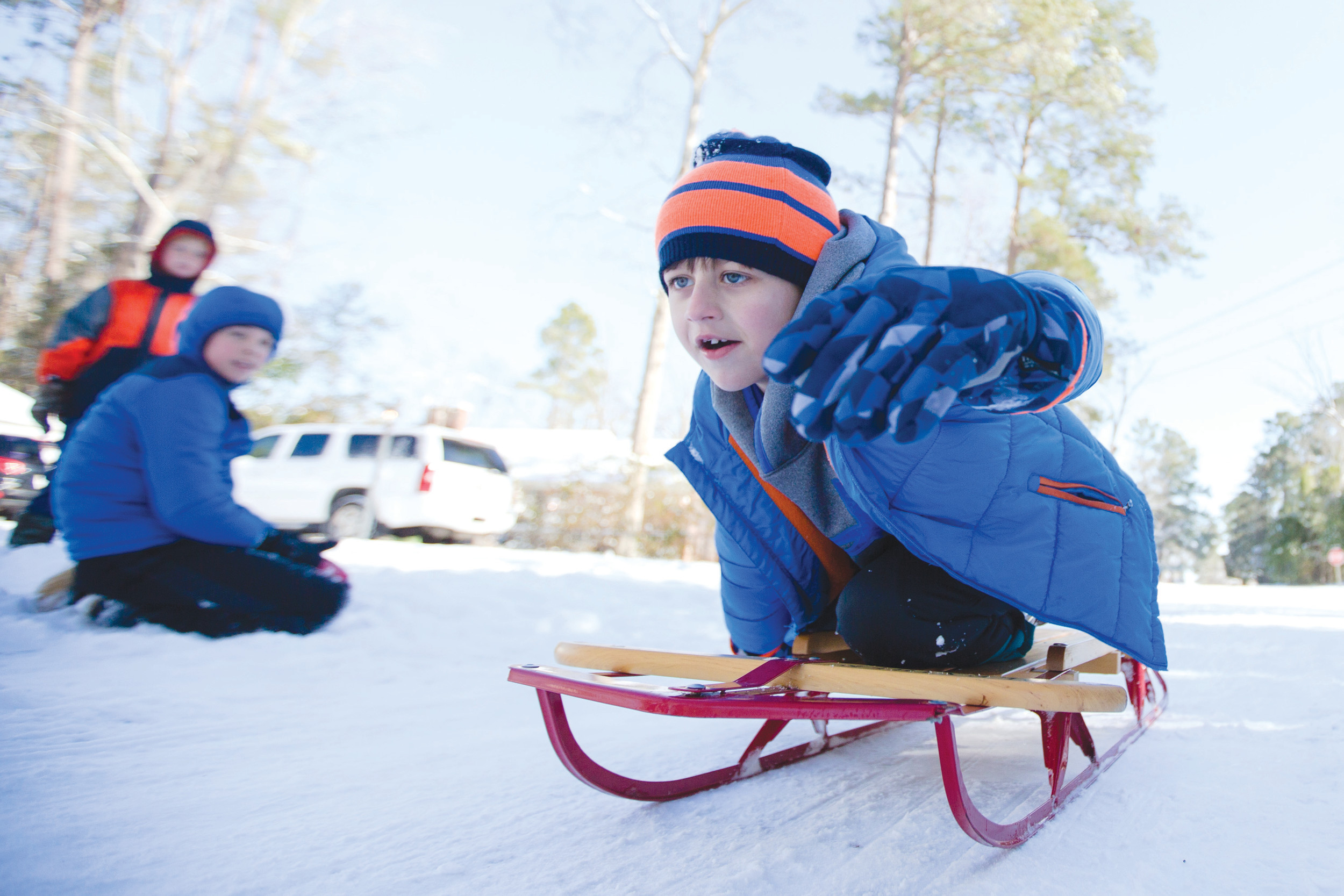 Grayson Sanders, 8, sleds past some friends down an icy road in Sumter.