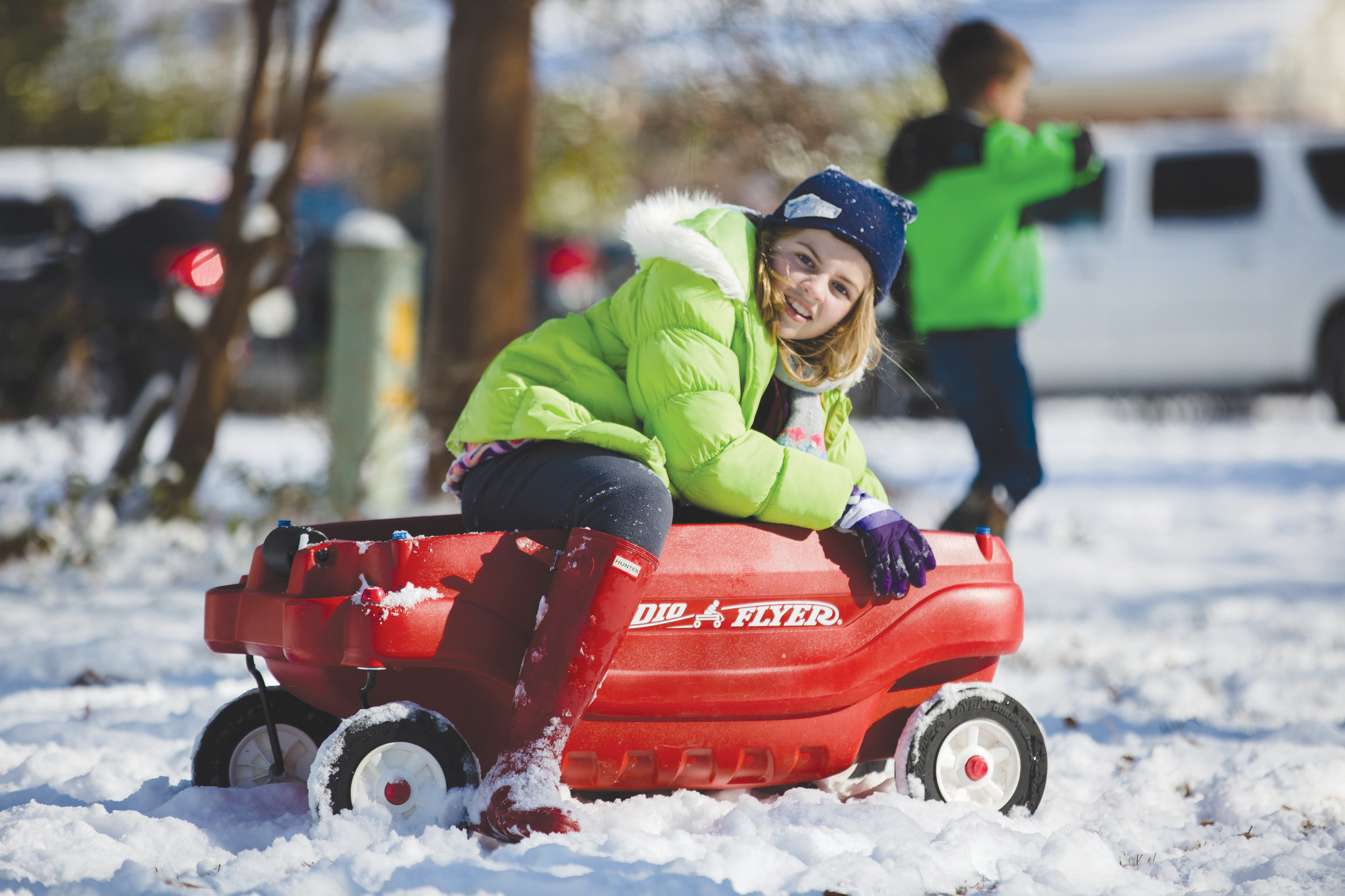 Paige Sanders climbs onto a red wagon in the snow while her friends sled on Thursday in Sumter.