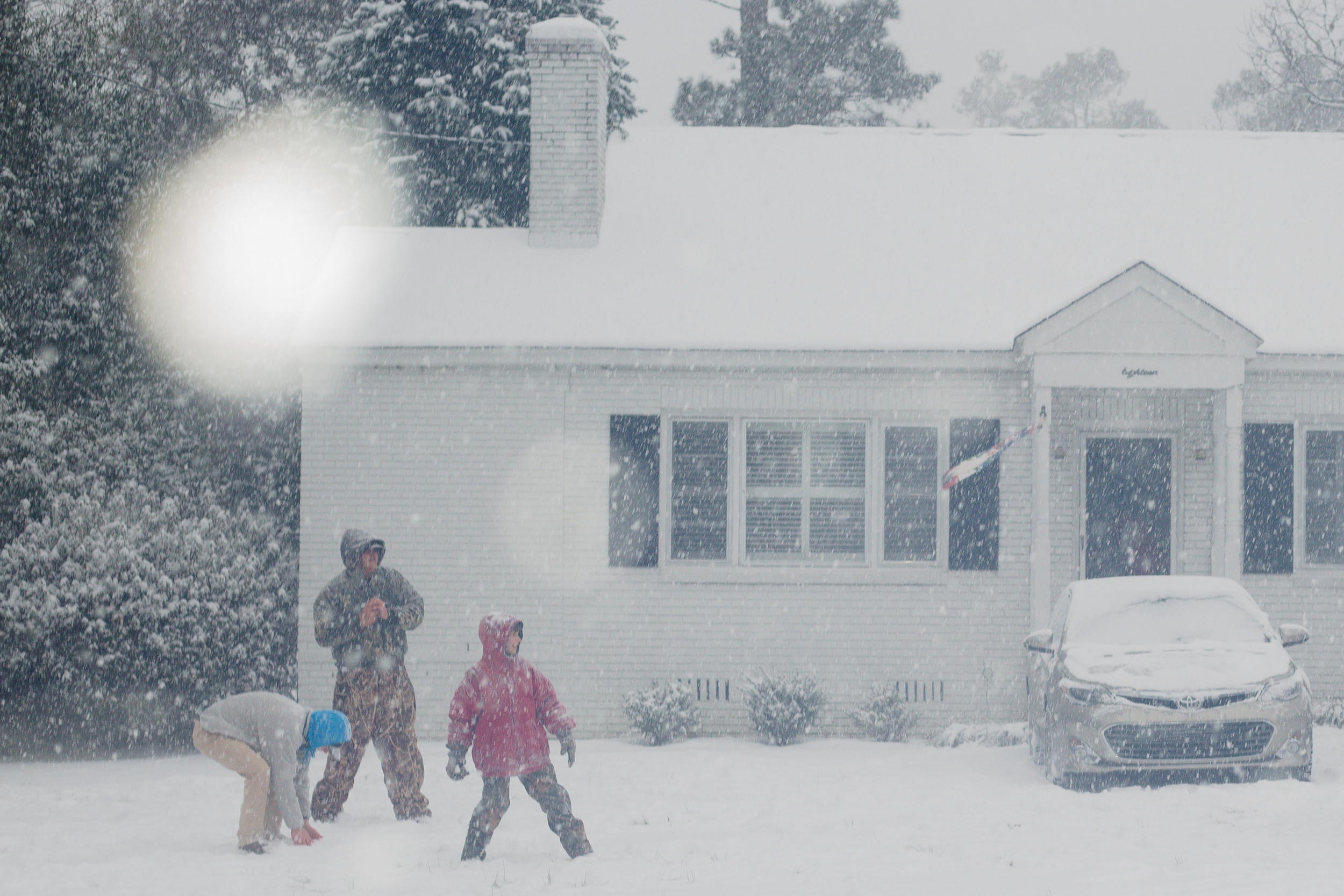 Cameron Henderson (left), William Chandler and Emmit Bilton ready themselves for a snowball fight in a front yard on Riley Street in Sumter Wednesday afternoon.