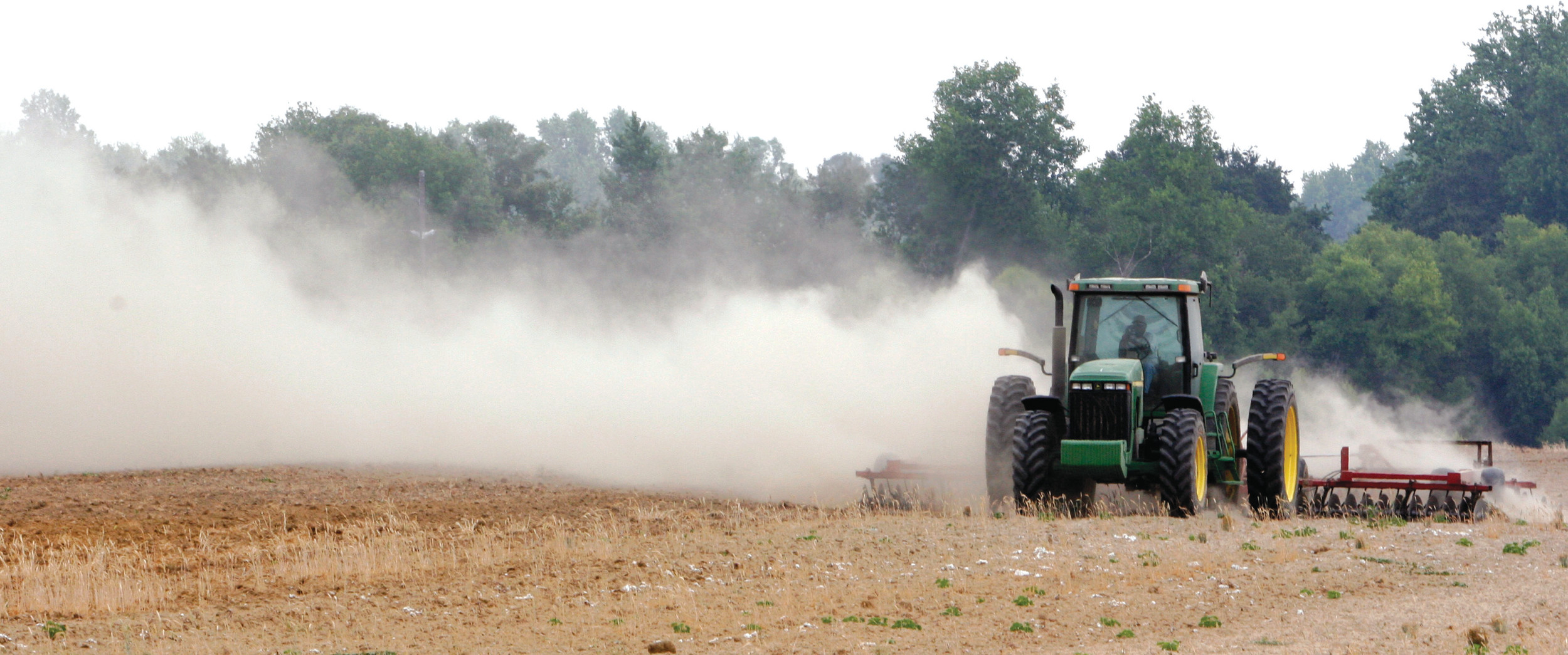 A farm tractor scatters dust in 2007 as it moves across a field on a farm along state road 82 near Tifton, Georgia. Soil is an important natural resource that must be preserved against loss by such forces as wind erosion.