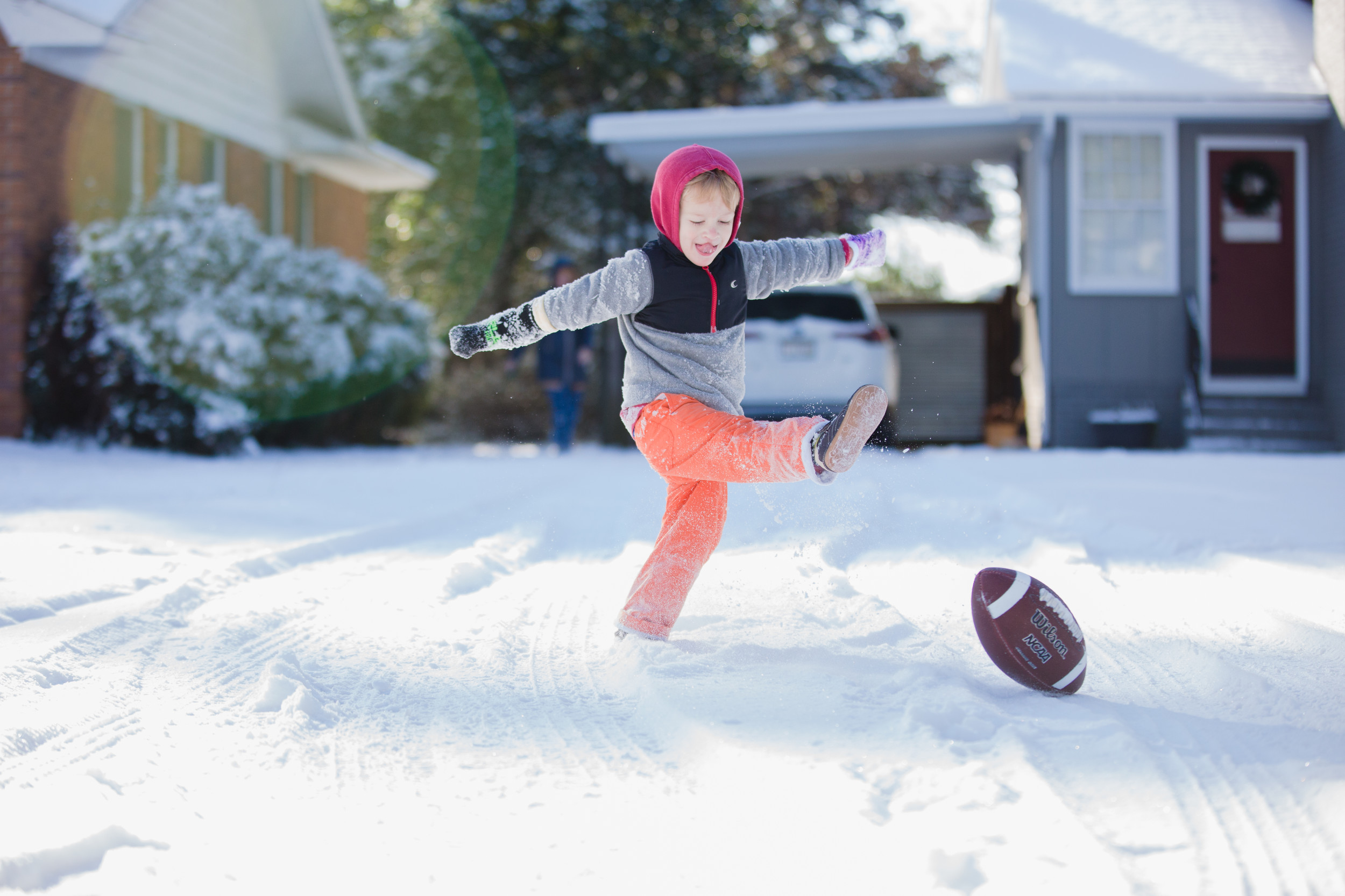 Max Bailey kicks a football in a front yard on Richardson Street on Thursday.