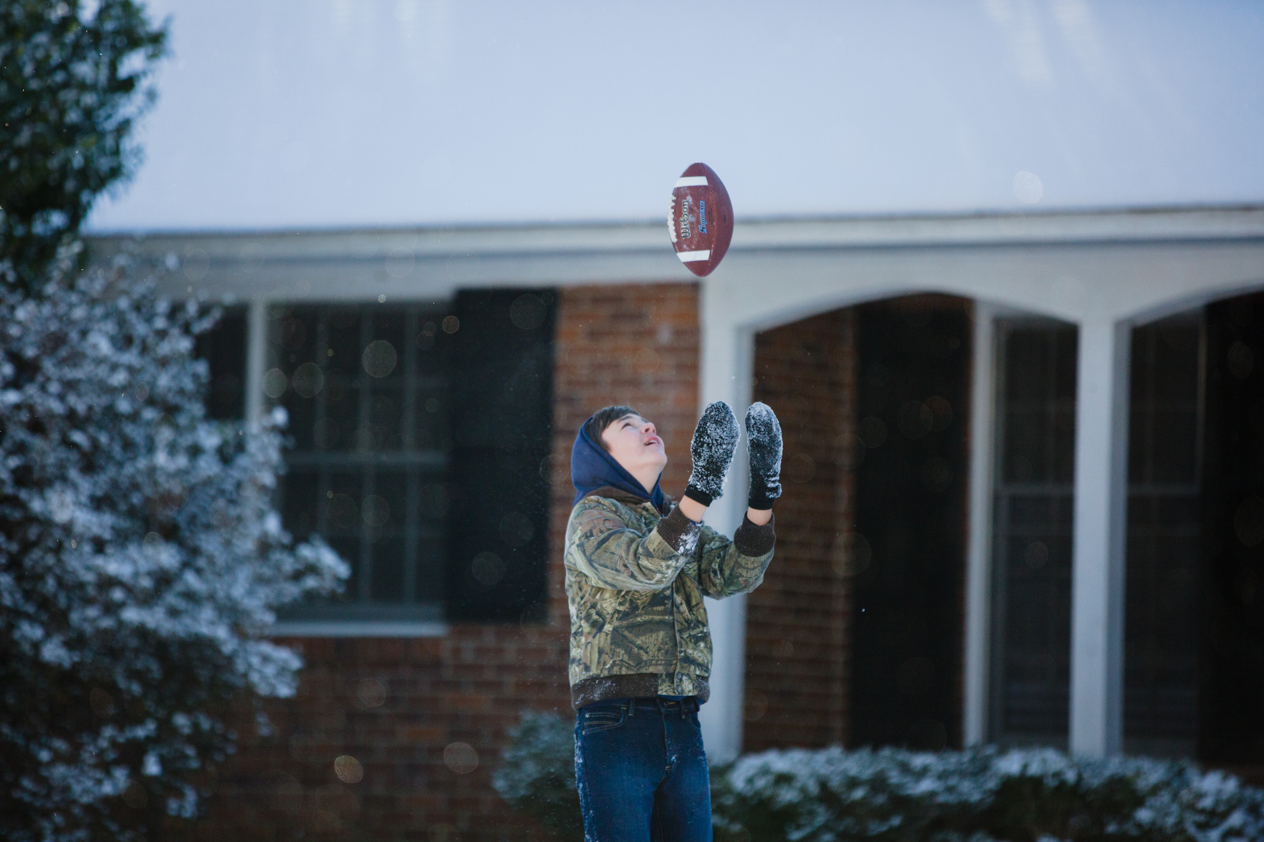 Trace Bailey tosses a football in a front yard on Richardson Street on Thursday morning.