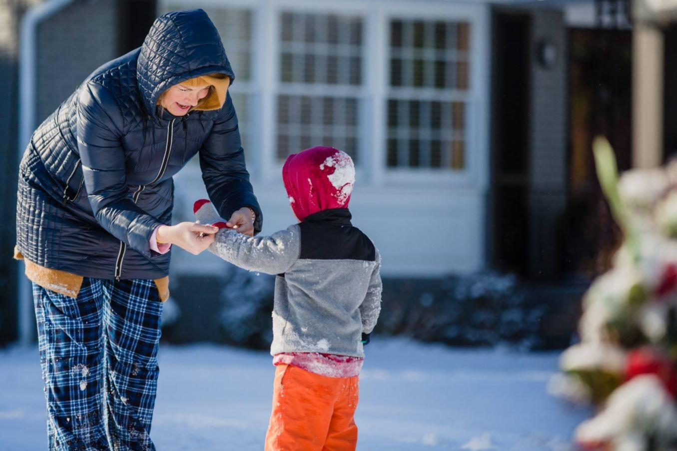 MICAH GREEN / THE SUMTER ITEMVictoria Bailey helps her son Max get on dry mittens Thursday morning in Sumter.