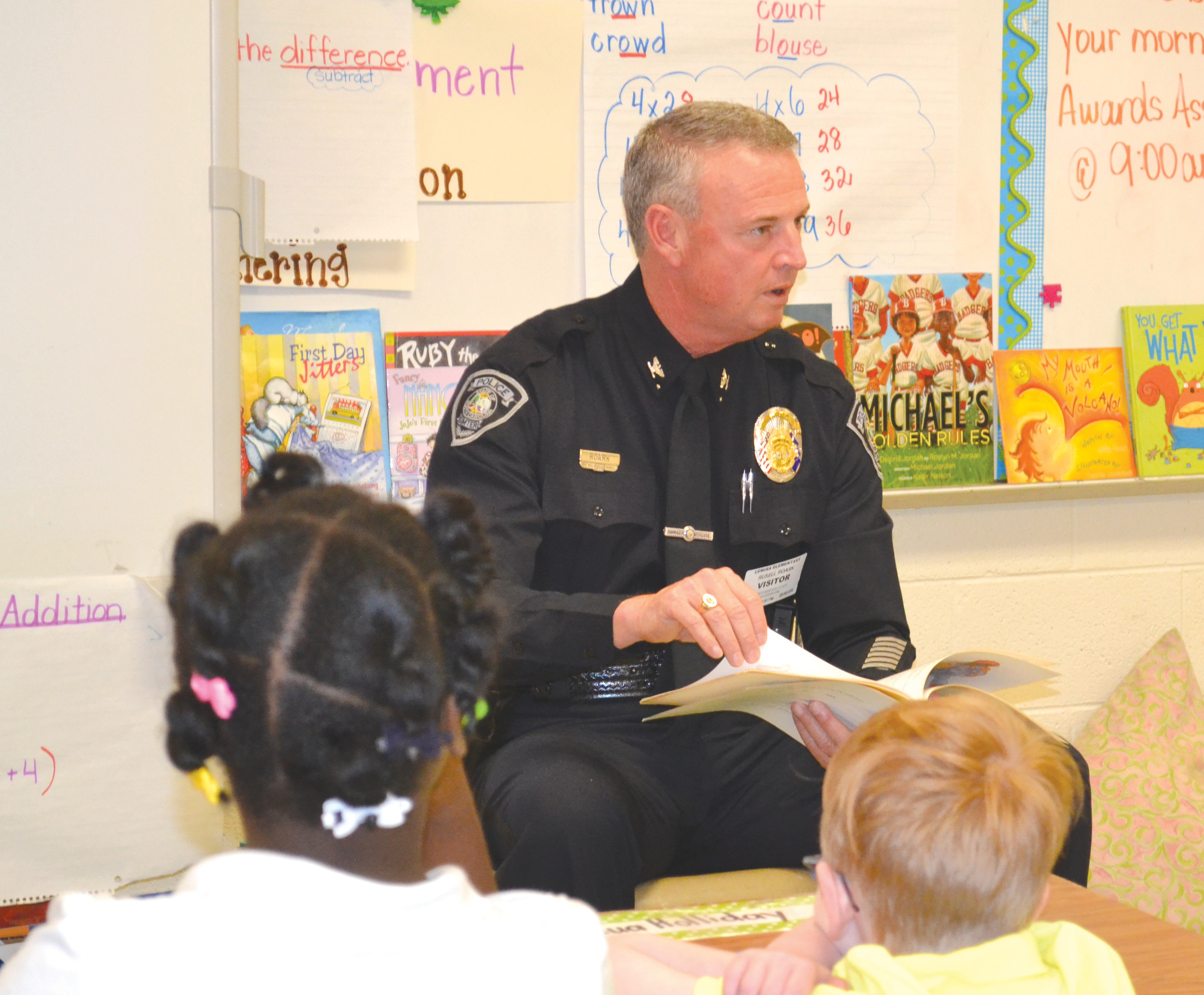 Chief Russell Roark reads to children at Lemira Elementary School recently.